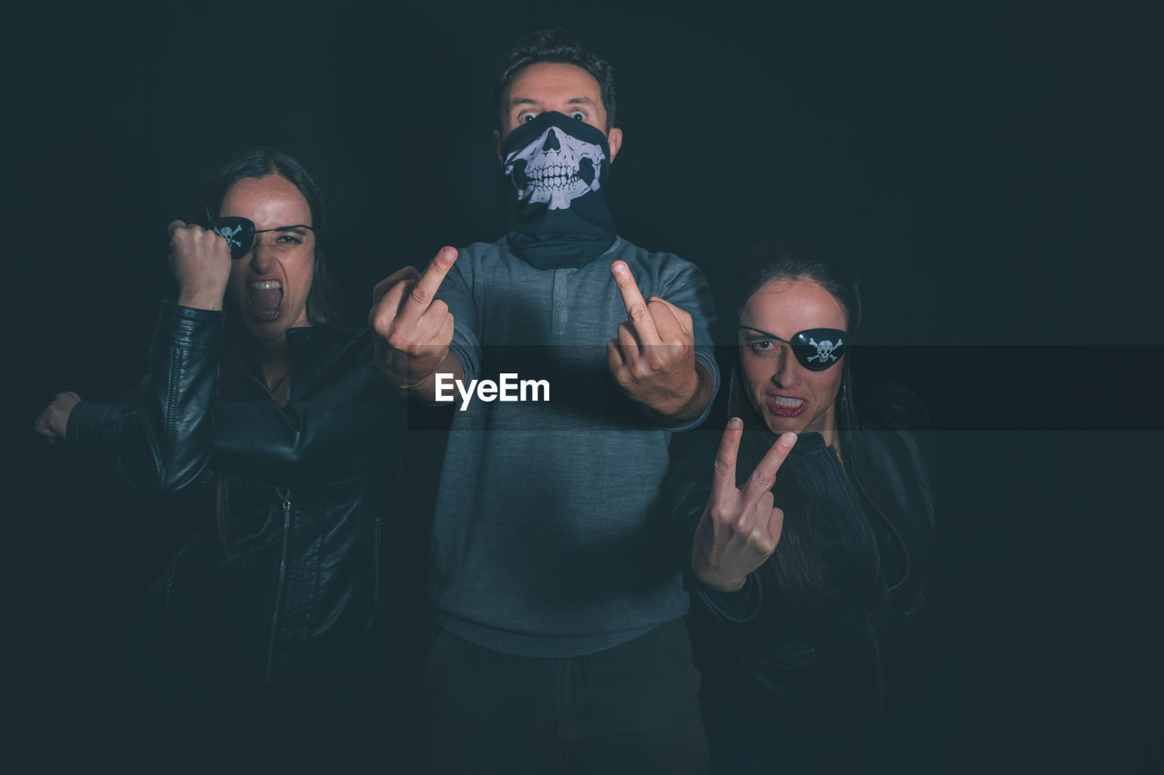 Portrait of friends wearing masks while standing against black background