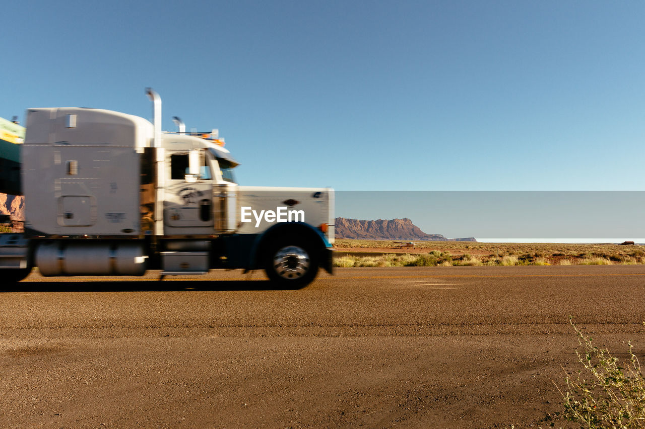transportation, land vehicle, sky, mode of transportation, landscape, environment, clear sky, road, truck, land, copy space, nature, semi-truck, no people, scenics - nature, desert, day, motor vehicle, freight transportation, non-urban scene, trucking, arid climate, climate