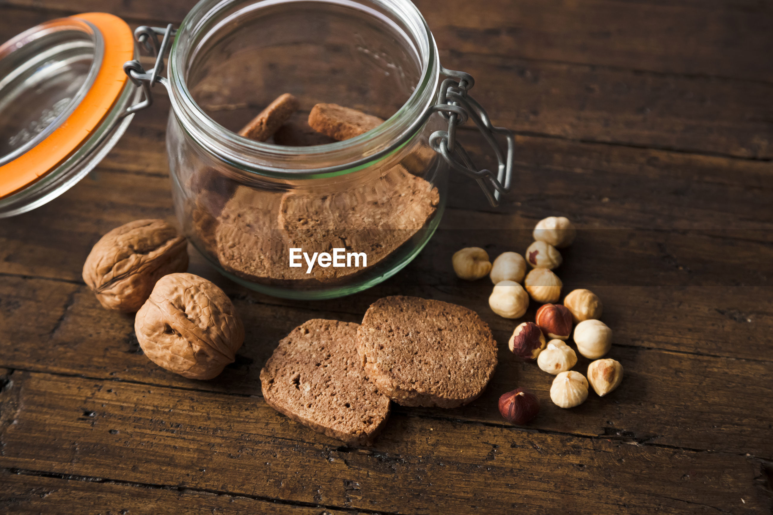 High angle view of cookies in jar by nuts on table