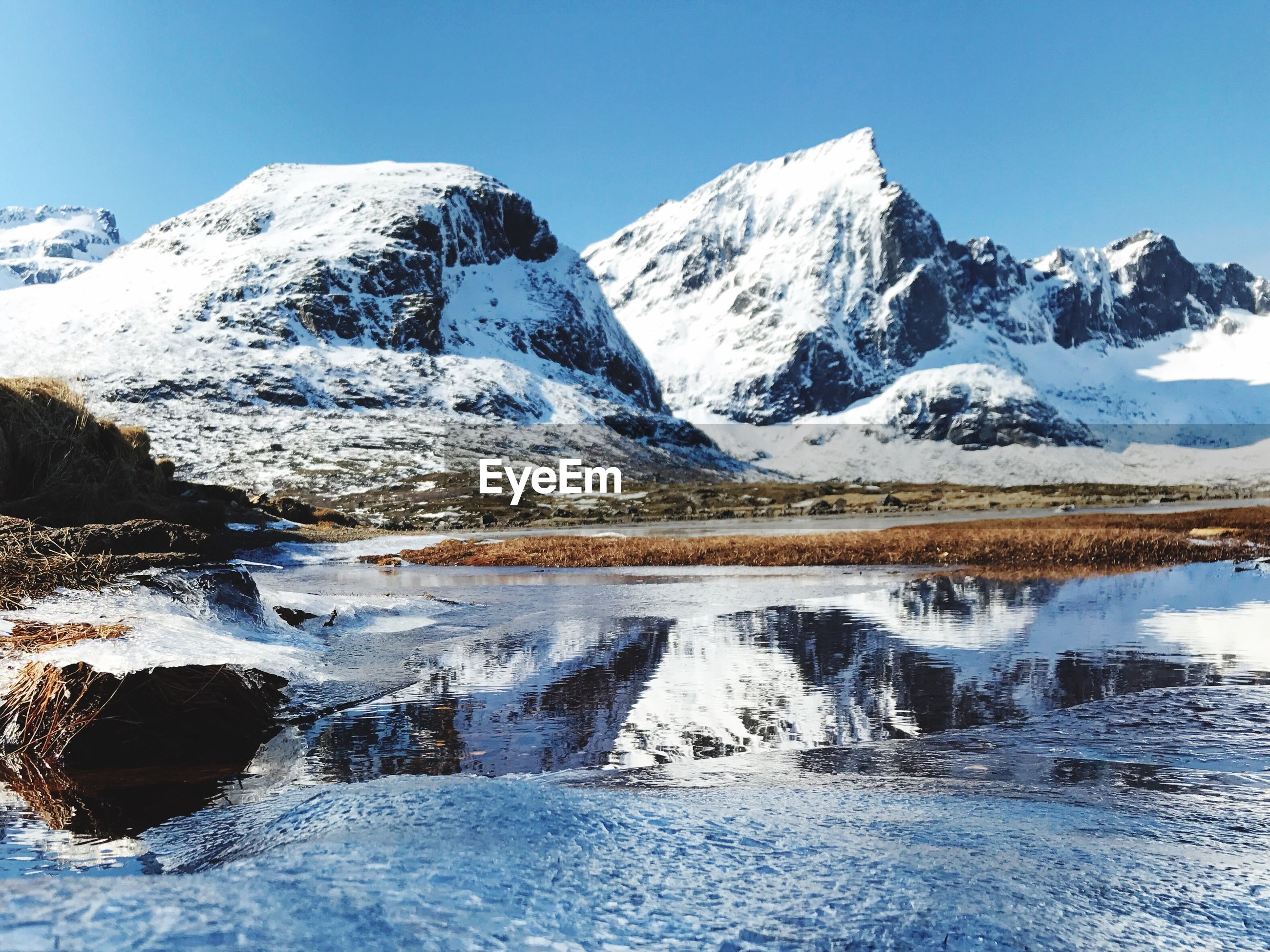 SCENIC VIEW OF FROZEN LAKE AGAINST SNOWCAPPED MOUNTAINS
