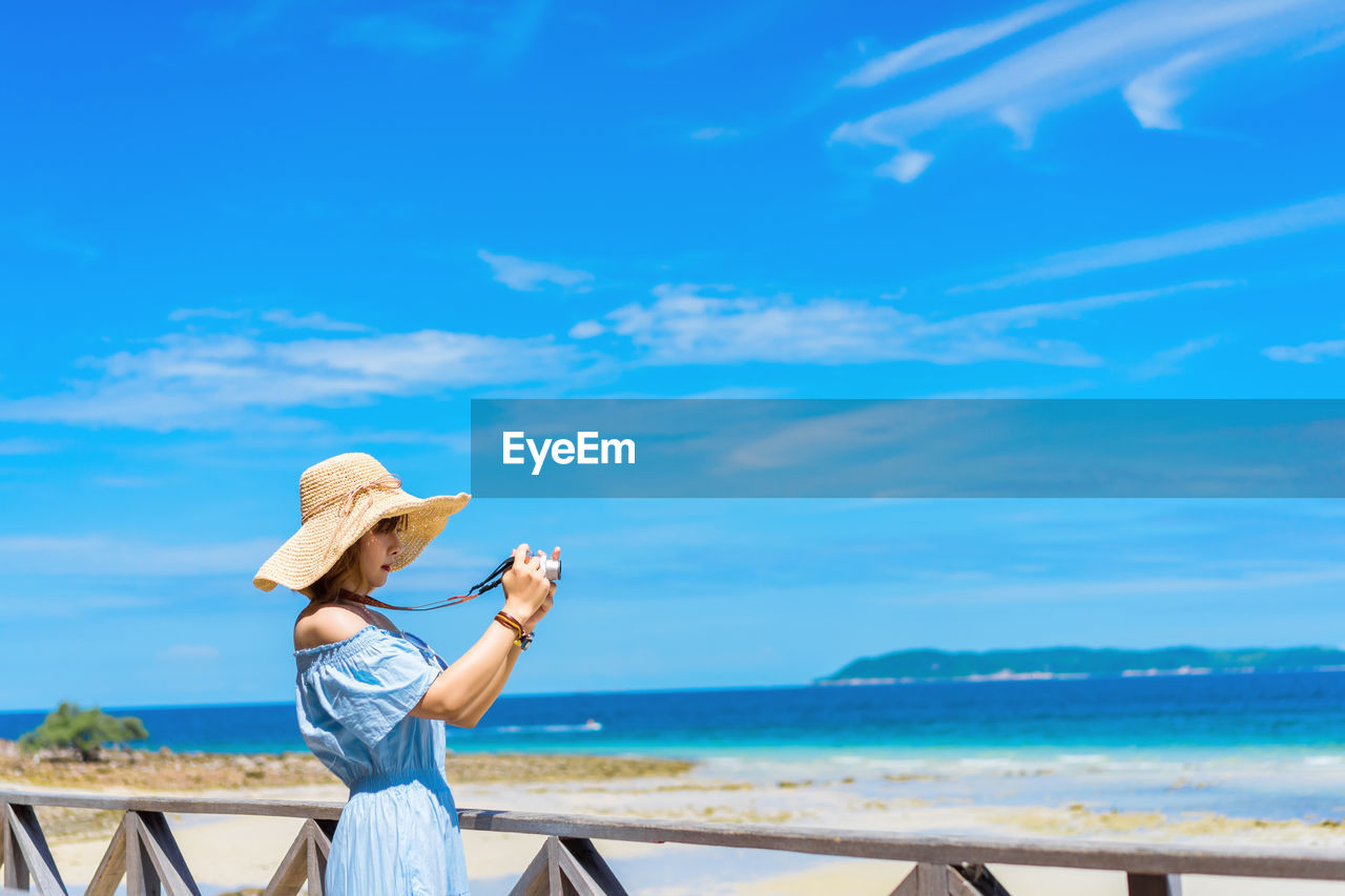Side view of woman photographing at beach against blue sky