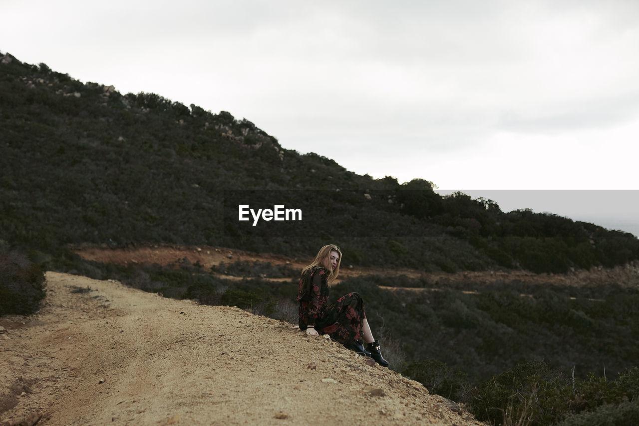 Teenage girl sitting on mountain against sky