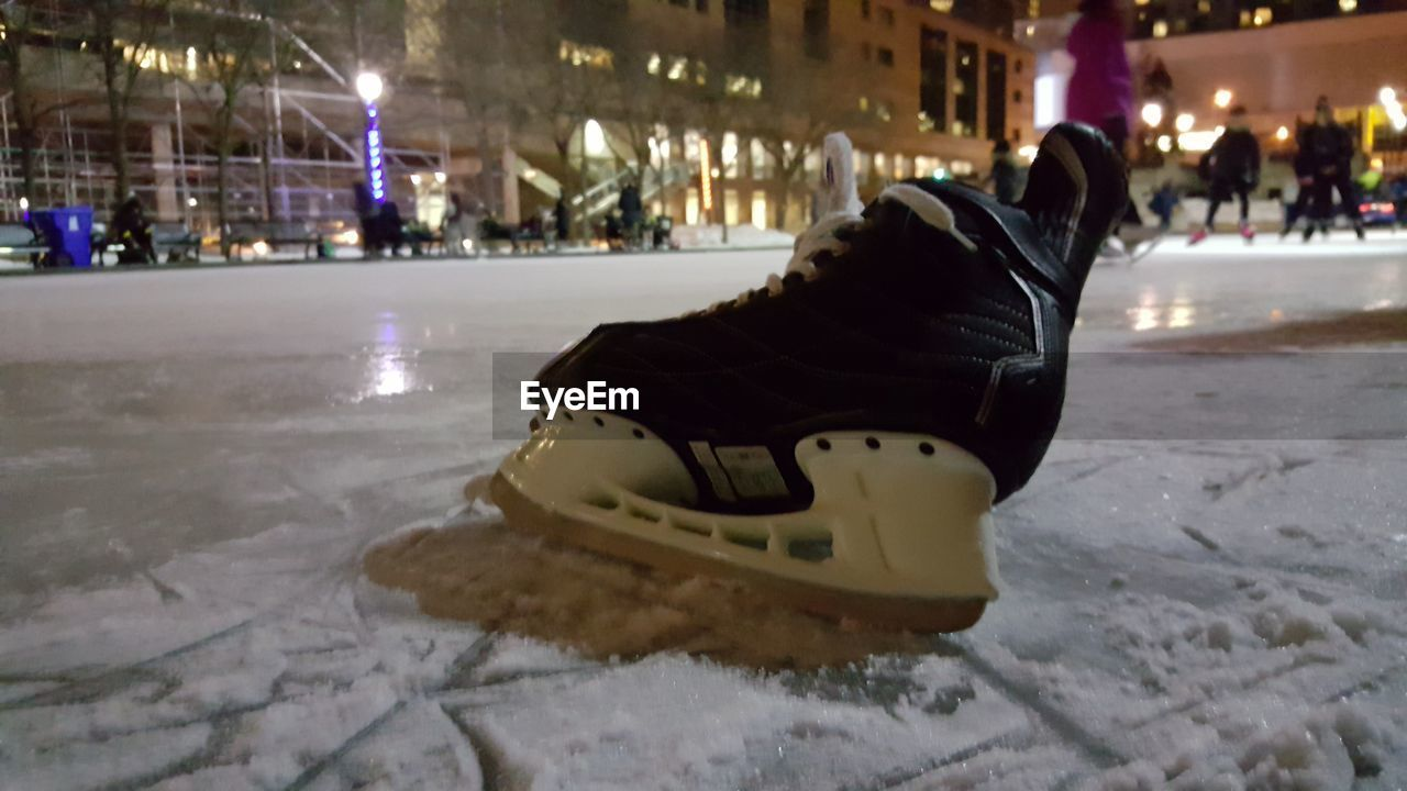 winter, cold temperature, snow, ice, ice-skating, ice rink, winter sport, incidental people, night, illuminated, ice skate, architecture, shoe, building exterior, focus on foreground, nature, built structure, sport, city, warm clothing
