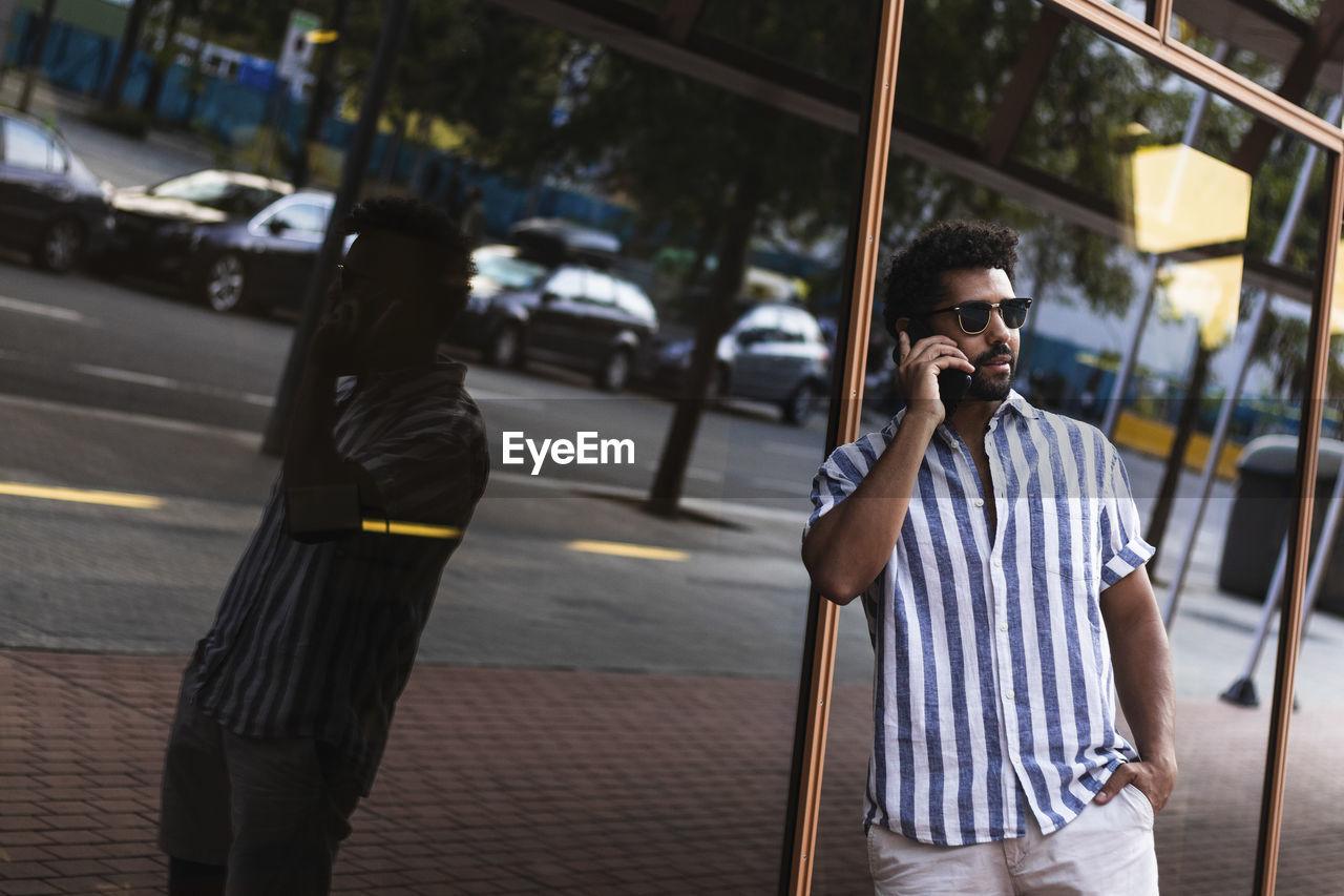 FULL LENGTH OF MAN HOLDING MOBILE PHONE ON STREET