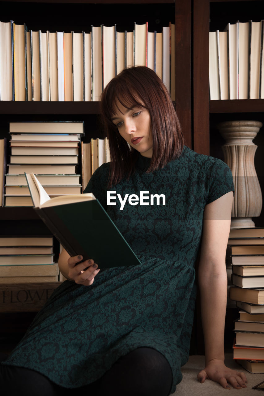 publication, book, real people, young adult, indoors, young women, one person, lifestyles, learning, casual clothing, sitting, education, women, leisure activity, reading, adult, shelf, bookshelf, teenager, hairstyle, literature, studying, beautiful woman