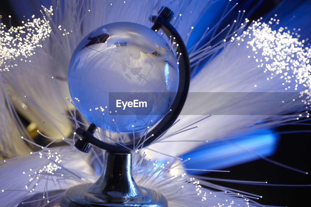LOW ANGLE VIEW OF CRYSTAL BALL IN ILLUMINATED GLASS