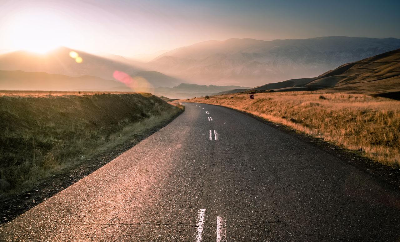 Road amidst landscape against sky during sunset