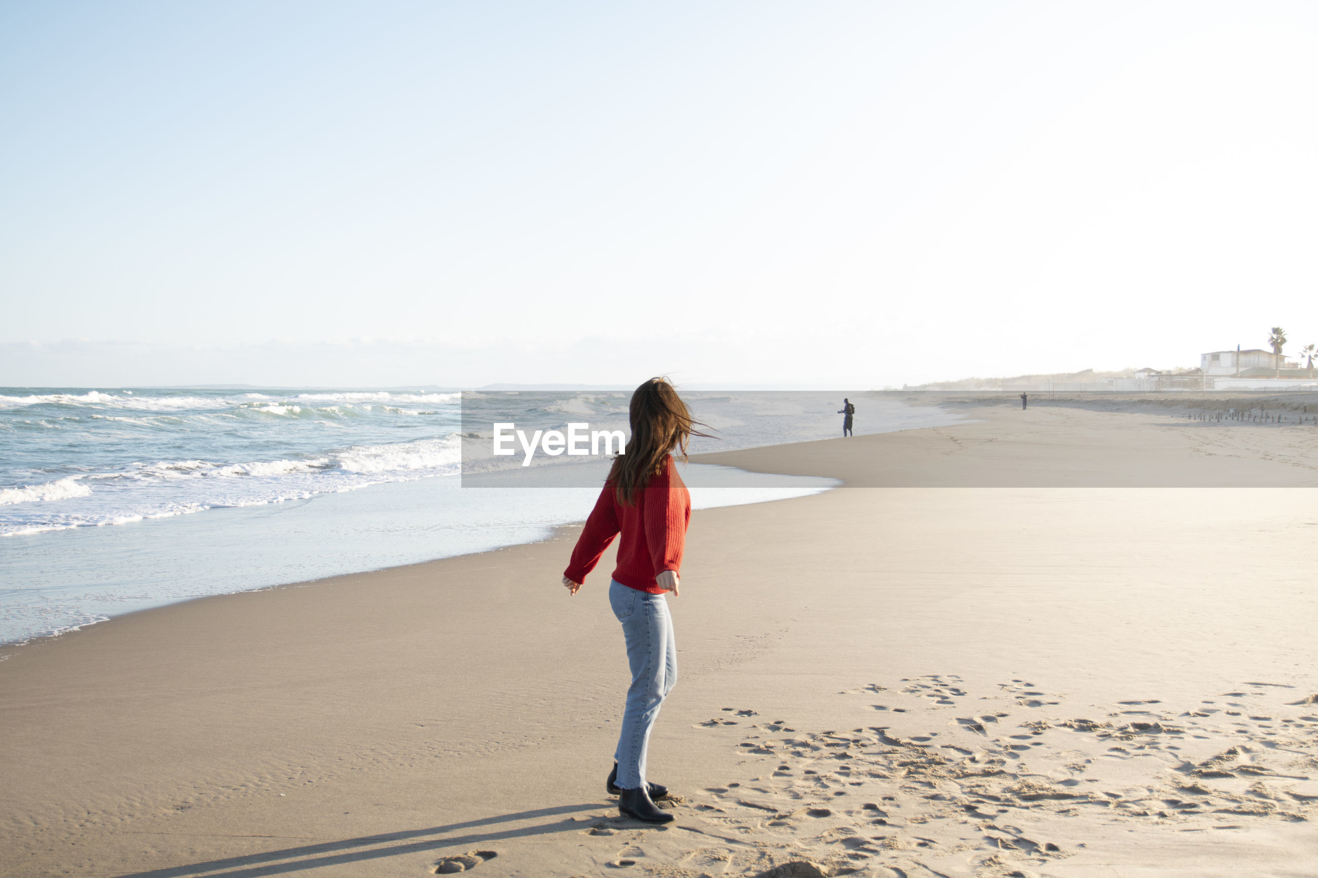 REAR VIEW OF WOMAN STANDING ON BEACH