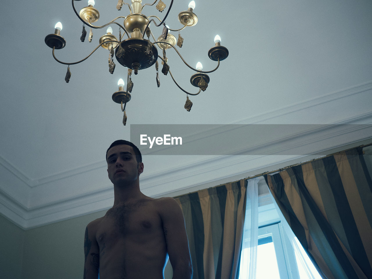 Low Angle View Of Shirtless Man Standing At Home