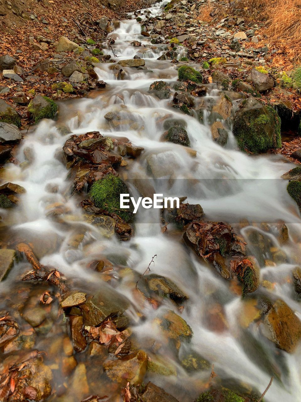 High angle view of stream flowing through rocks