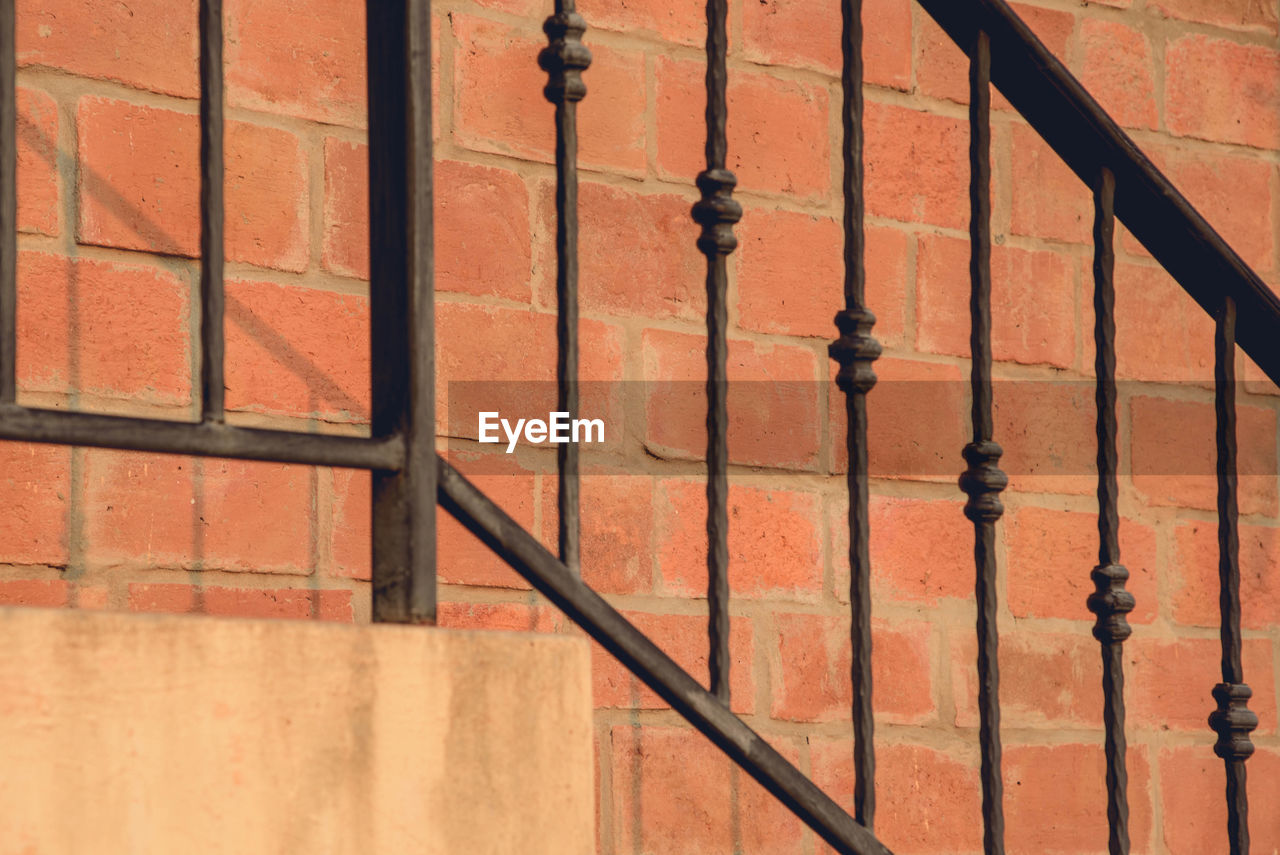 wall - building feature, architecture, built structure, shadow, no people, metal, railing, full frame, pattern, day, security, safety, sunlight, protection, building exterior, wall, outdoors, orange color, brick, close-up, wrought iron