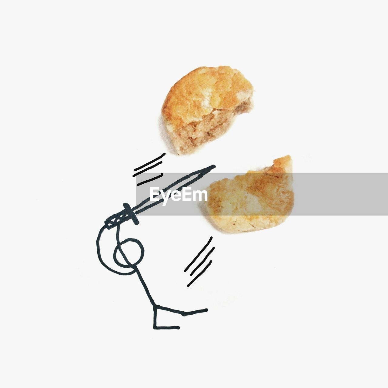Close-Up Of Stick Figure Cutting Bread On White Paper