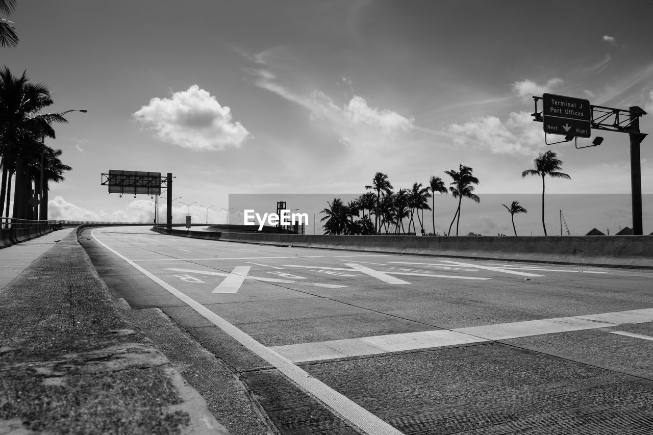 sign, sky, road, transportation, cloud - sky, symbol, road marking, direction, marking, nature, the way forward, tree, tropical climate, no people, communication, palm tree, city, street, empty, guidance, outdoors, dividing line