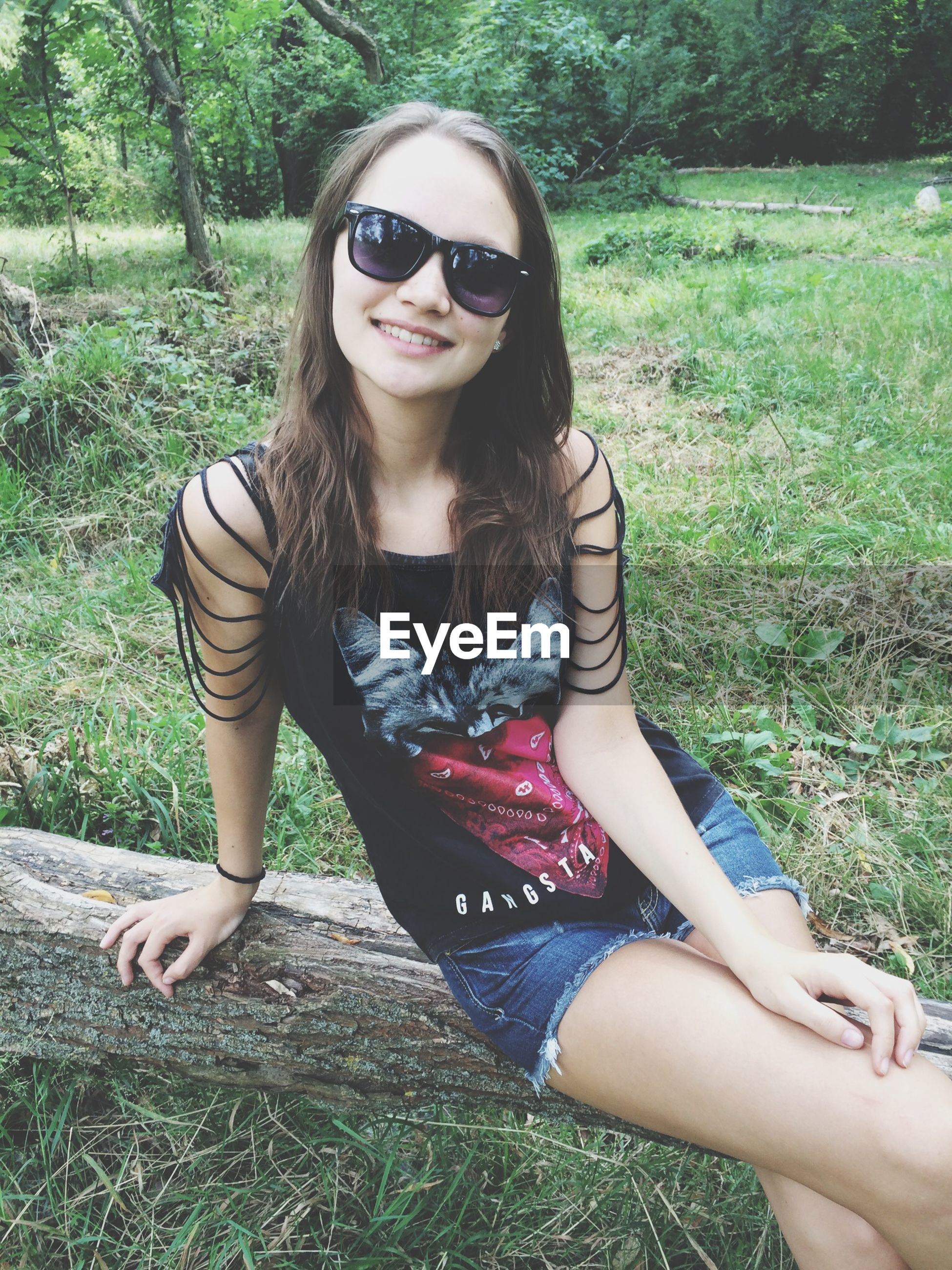 young adult, looking at camera, portrait, person, lifestyles, leisure activity, young women, front view, casual clothing, smiling, sunglasses, tree, sitting, happiness, holding, three quarter length, toothy smile