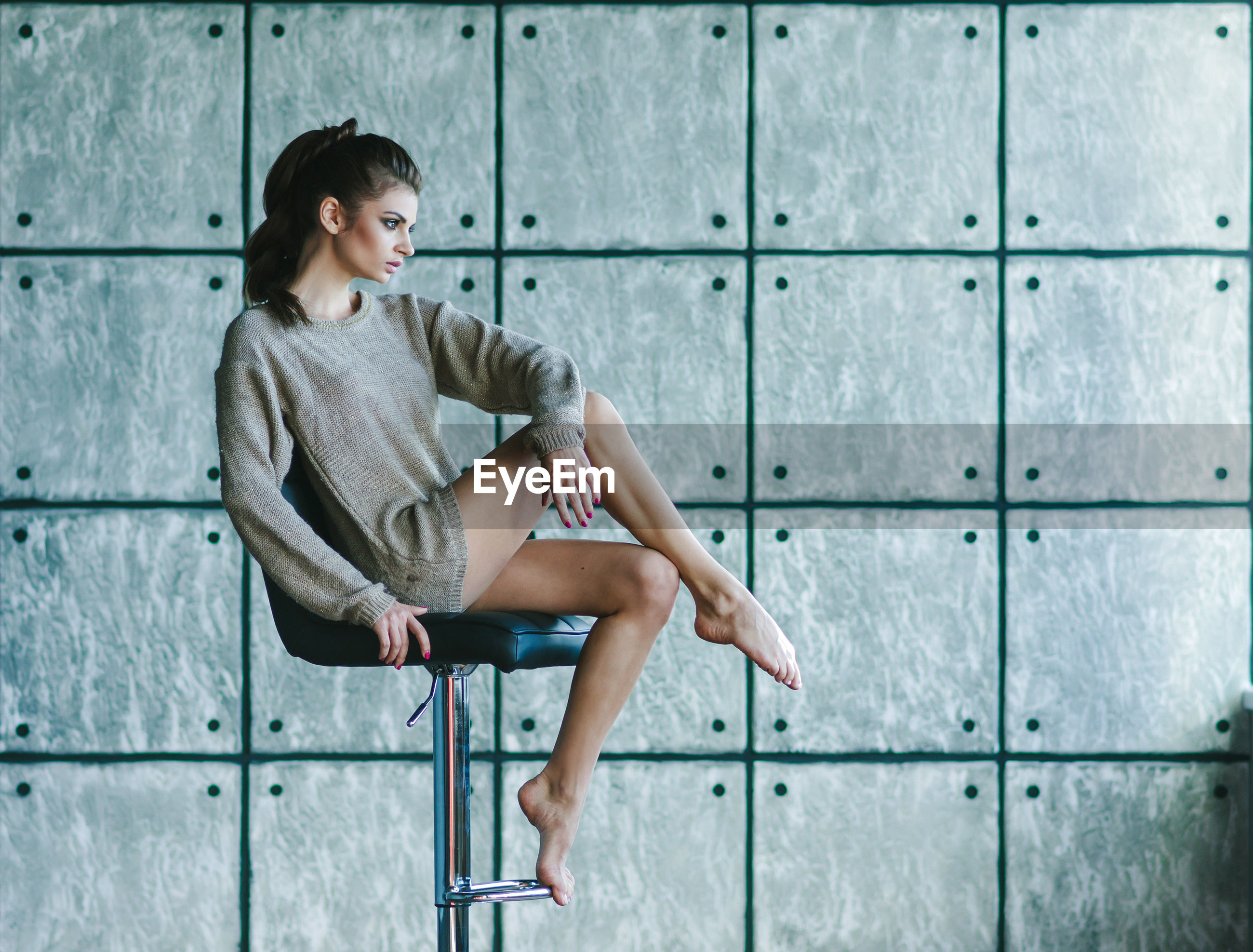 Full length of young woman sitting on chair against concrete wall