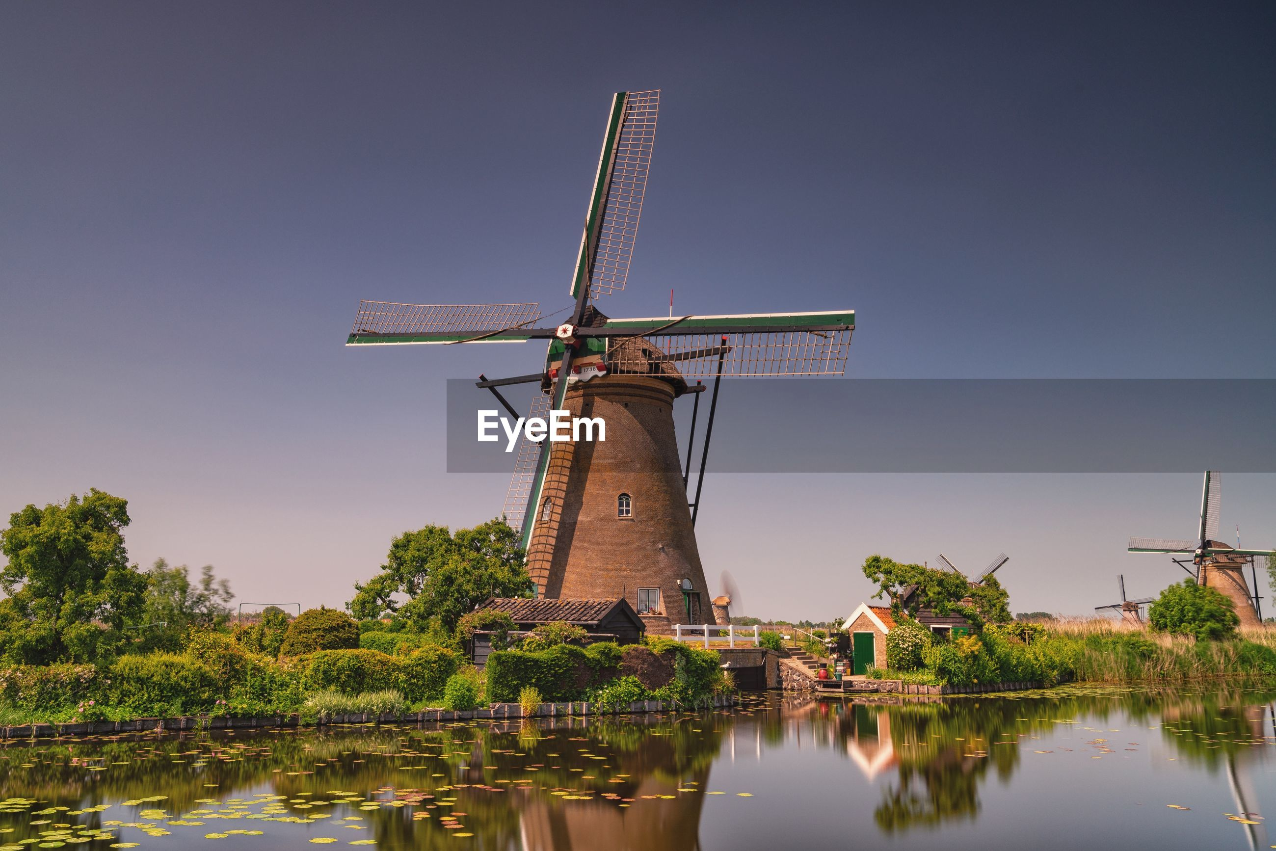 Traditional windmill by lake against clear sky