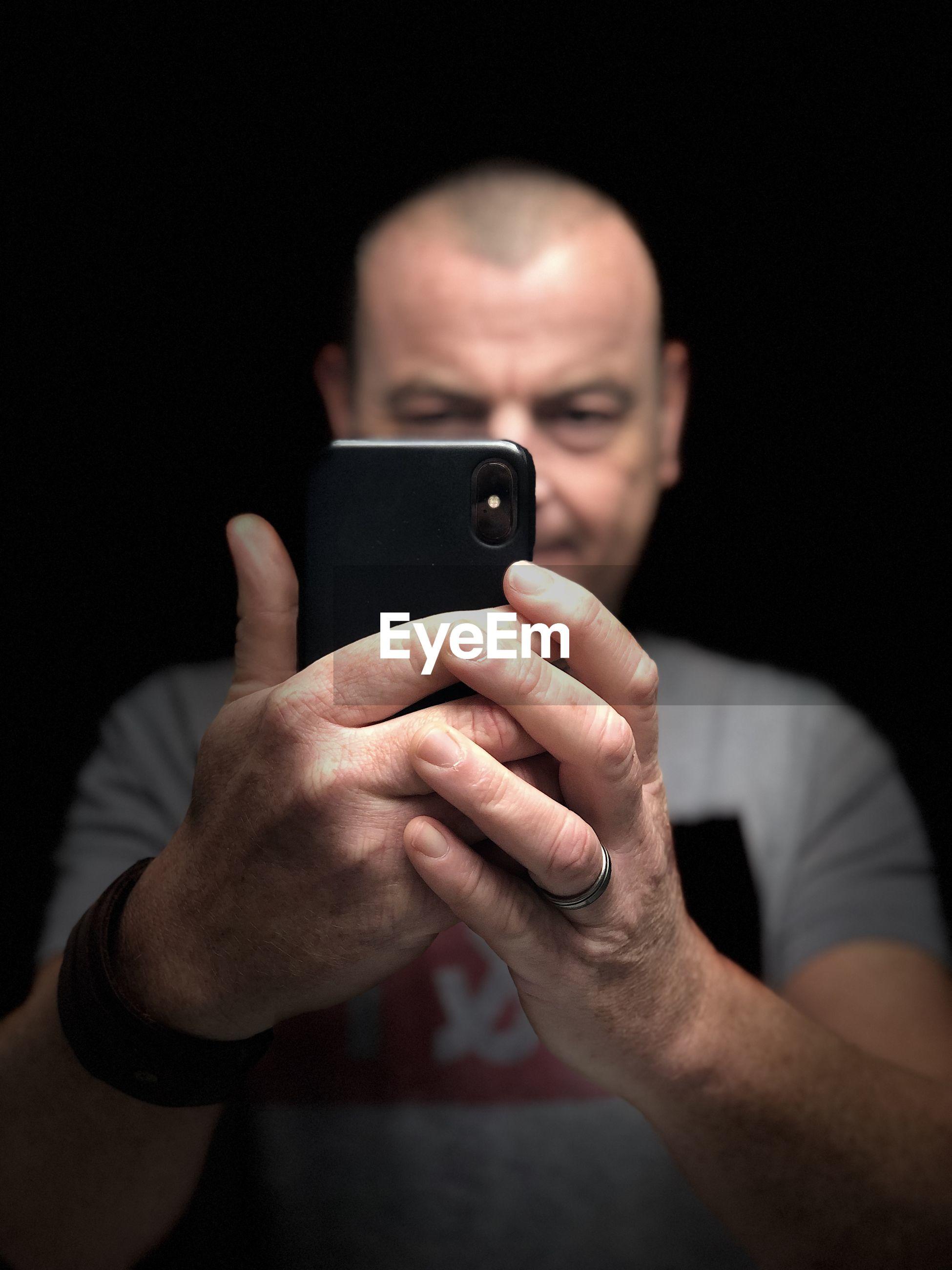 Portrait of man using mobile phone against black background