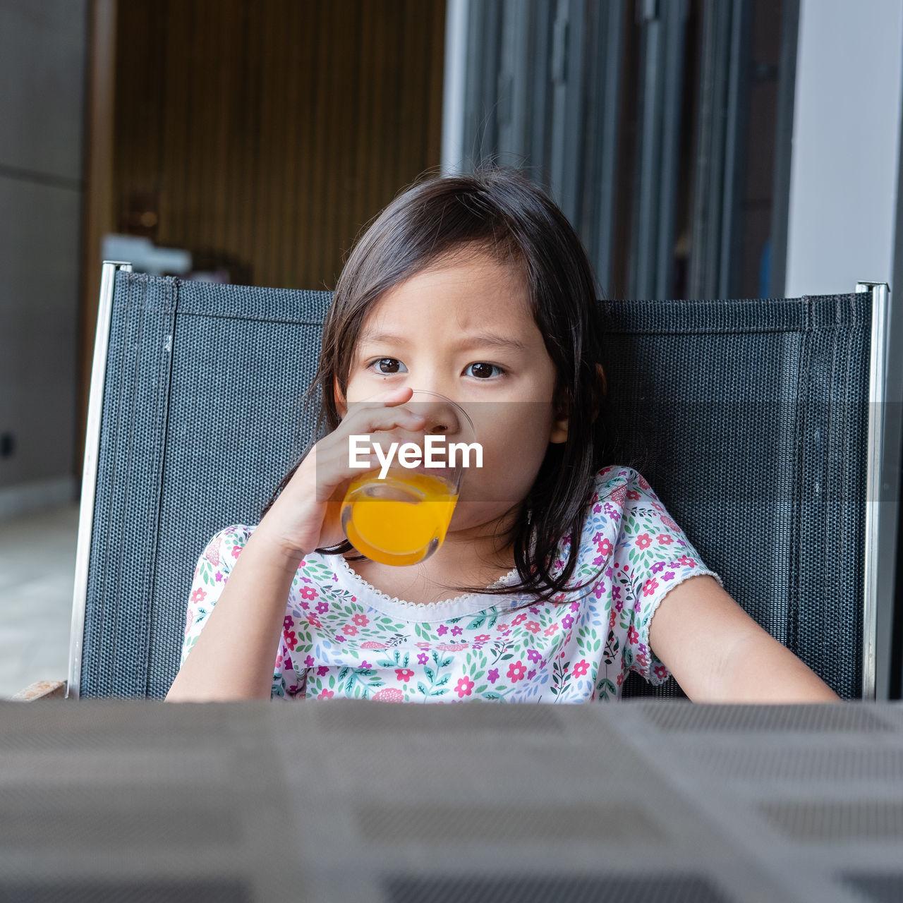 Girl Having Orange Juice While Sitting On Chair