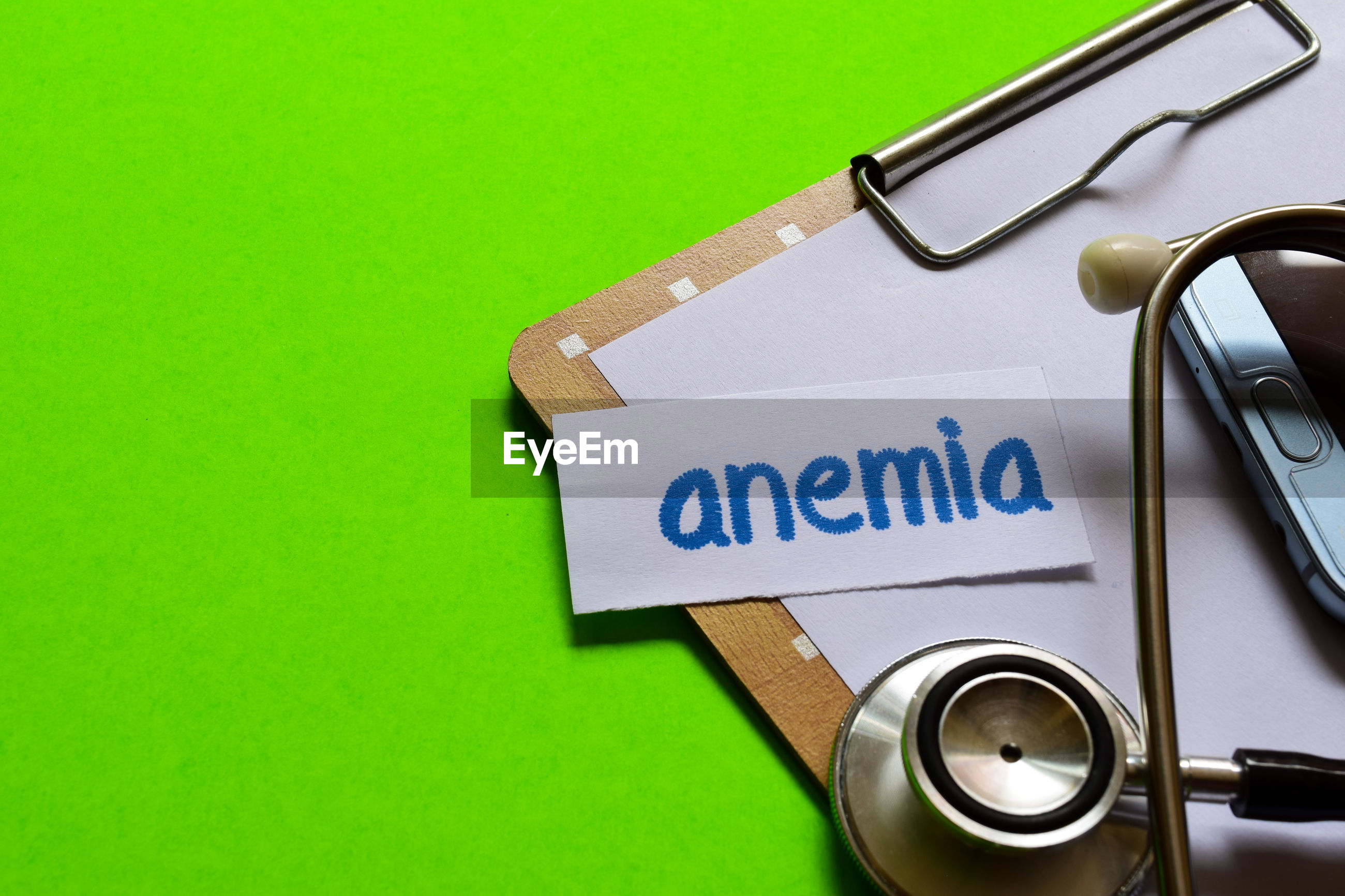 High angle view of anemia text on paper with clipboard and stethoscope over green background