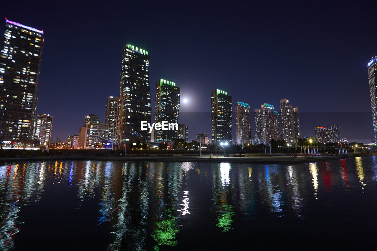 built structure, architecture, building exterior, city, night, water, illuminated, waterfront, sky, reflection, urban skyline, office building exterior, landscape, nature, building, river, skyscraper, cityscape, tall - high, no people, modern, outdoors, financial district, nightlife