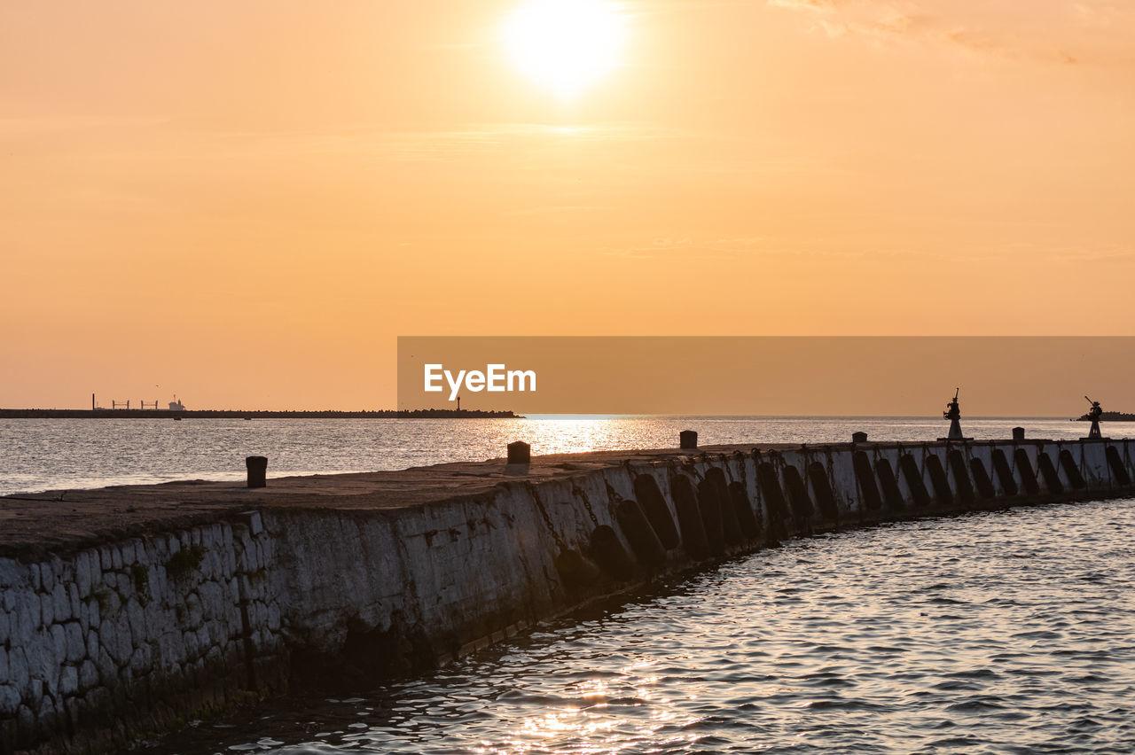 water, sky, sunset, sea, scenics - nature, beauty in nature, horizon, horizon over water, sun, orange color, nature, tranquil scene, tranquility, sunlight, non-urban scene, pier, idyllic, waterfront, incidental people, groyne, outdoors, wooden post