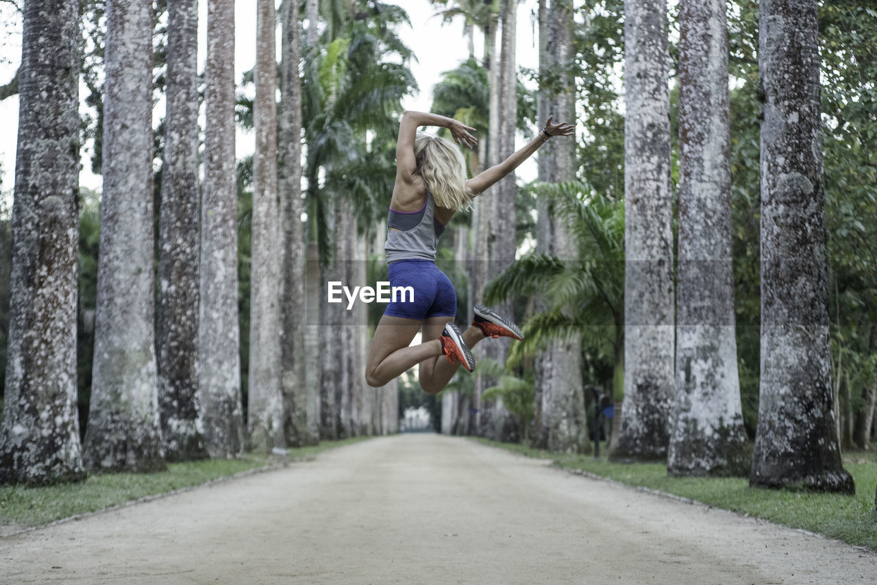 Woman Jumping On Road Amidst Tree Trunk