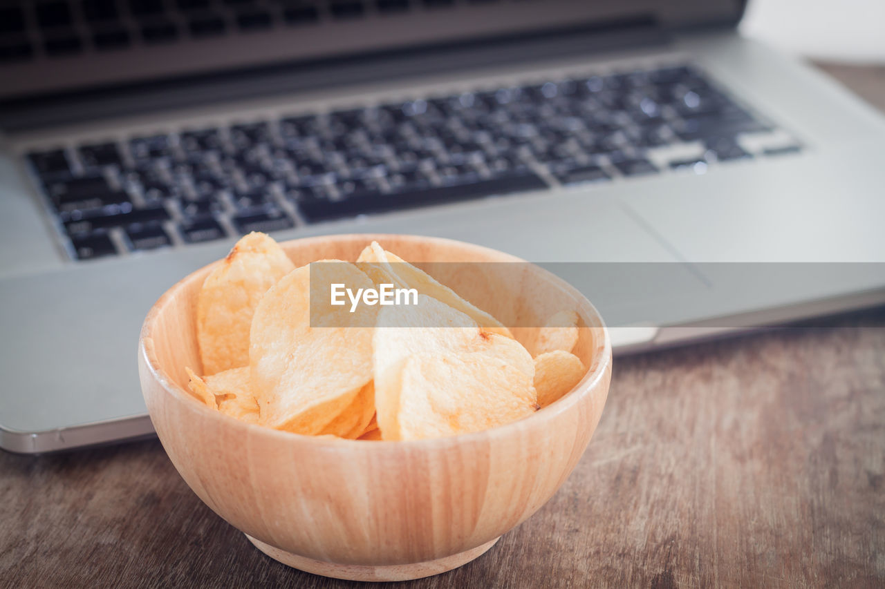 Close-up of wafers in bowl against laptop on table
