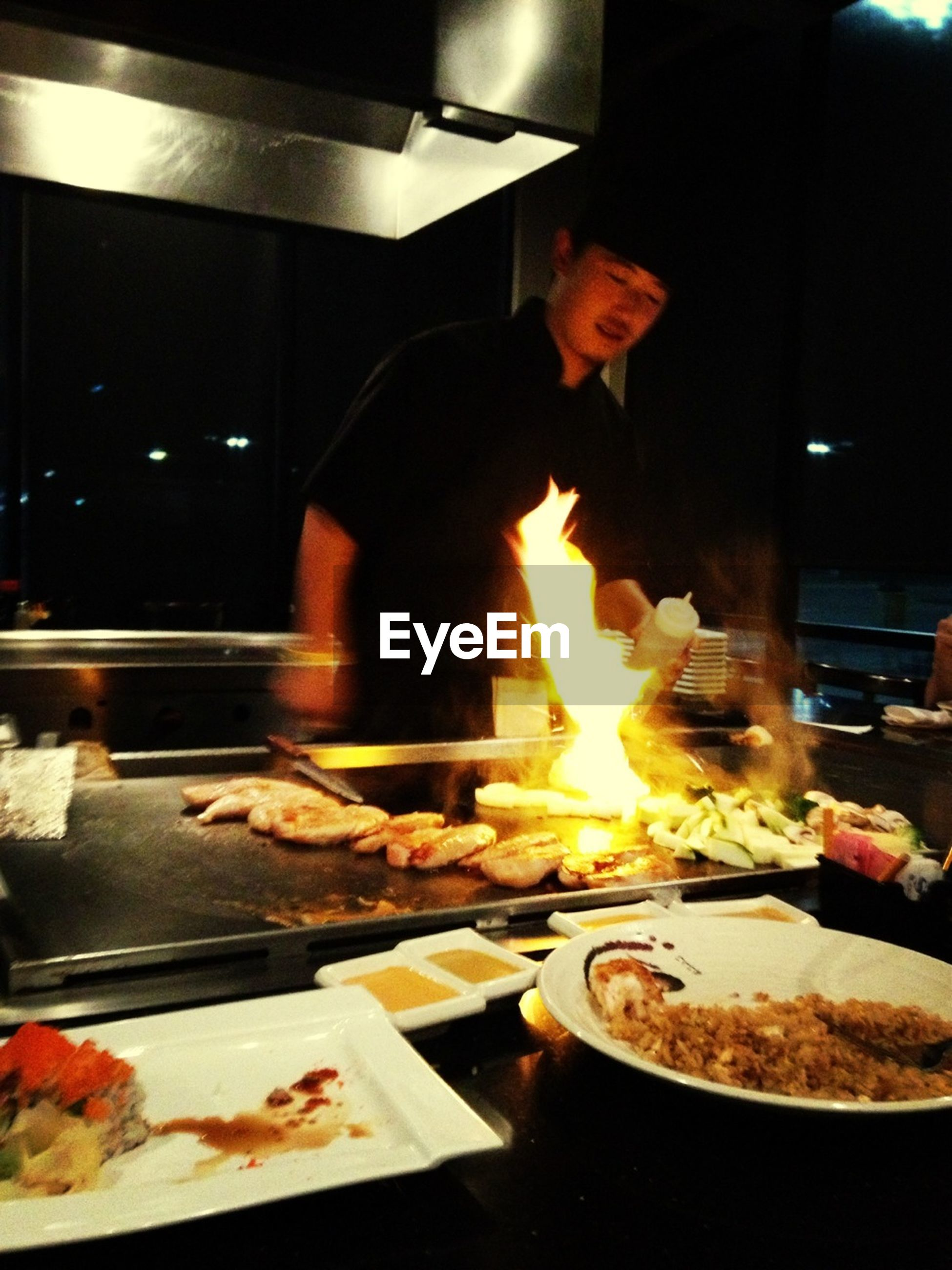 food and drink, food, indoors, freshness, preparation, lifestyles, heat - temperature, preparing food, meat, cooking, men, flame, restaurant, ready-to-eat, healthy eating, meal, person, table