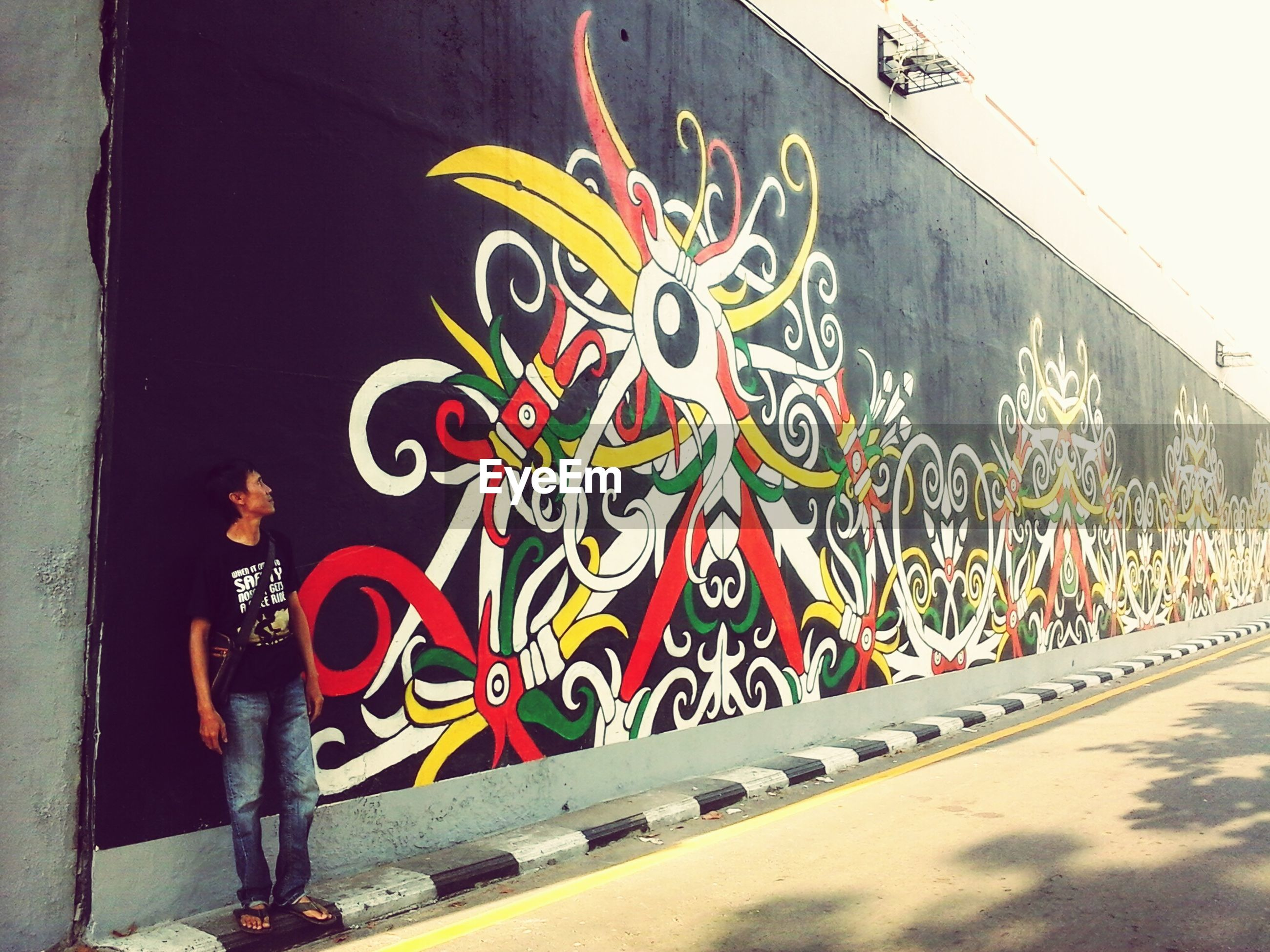 graffiti, art, art and craft, creativity, multi colored, wall - building feature, street, lifestyles, architecture, built structure, men, street art, building exterior, standing, sidewalk, human representation, full length, walking