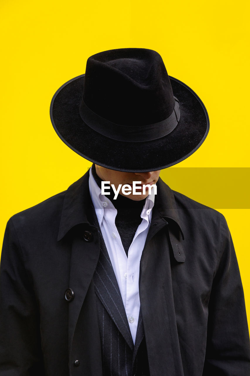 clothing, hat, suit, one person, front view, formalwear, yellow, studio shot, well-dressed, indoors, real people, business, black color, wall - building feature, men, portrait, waist up, standing, adult, obscured face, menswear