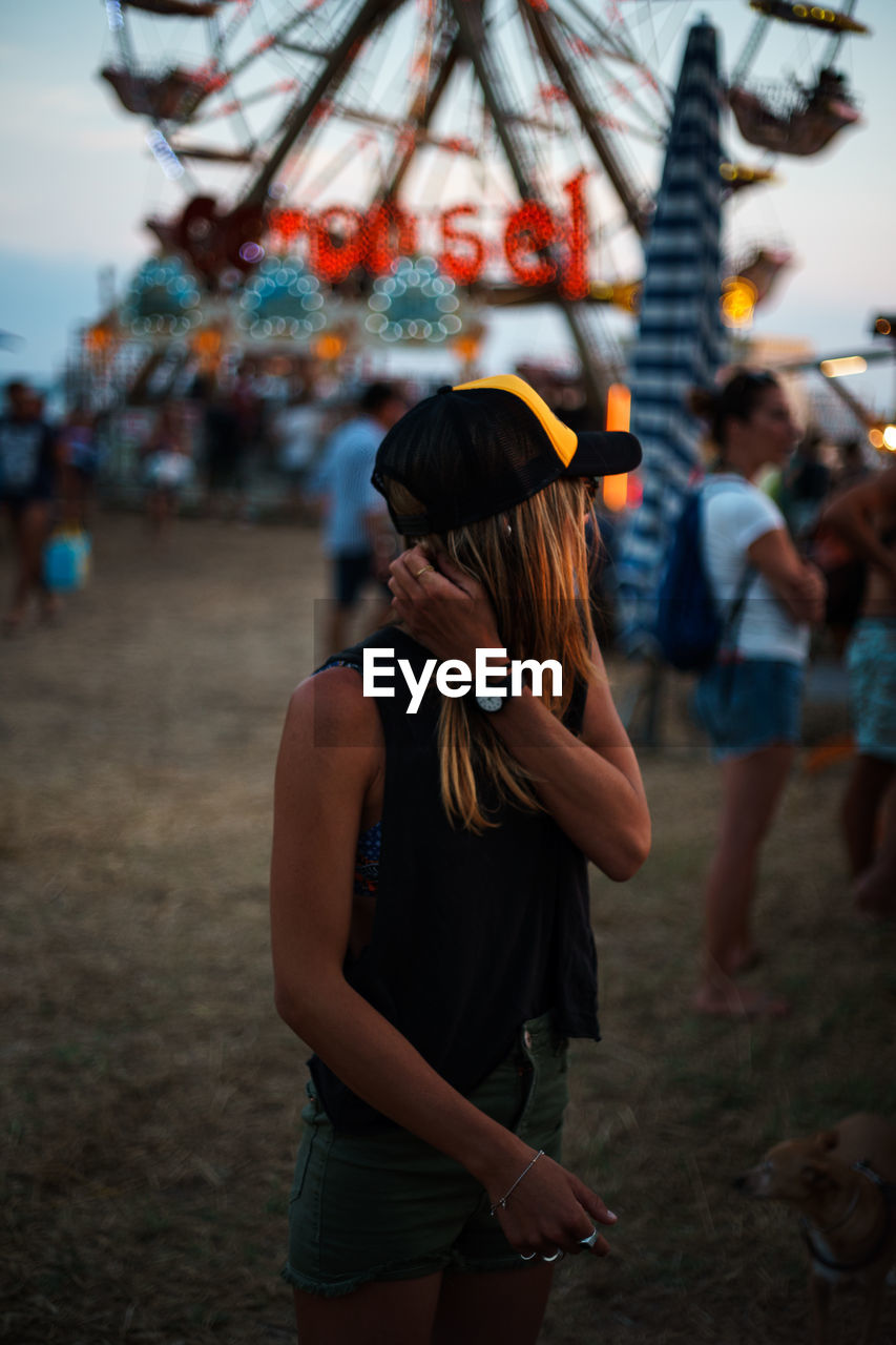 Woman Standing In Amusement Park At Dusk