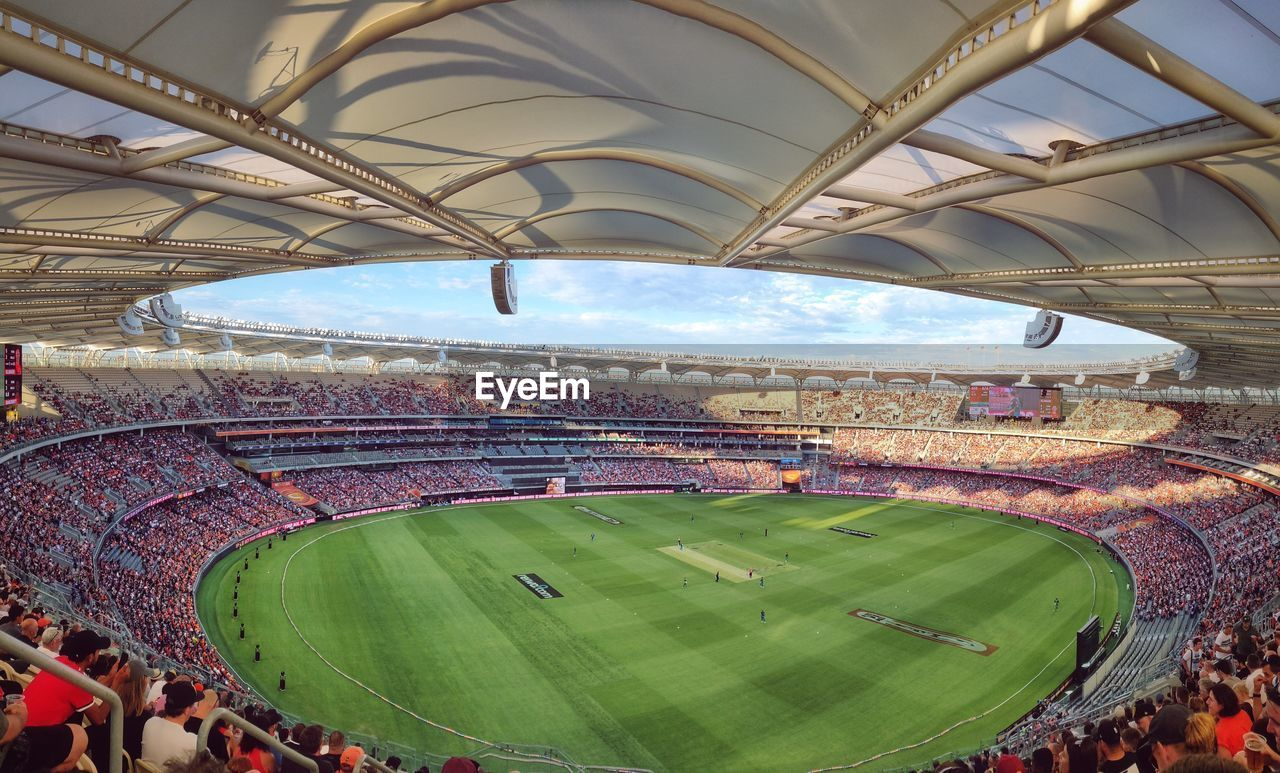 sport, group of people, crowd, stadium, large group of people, real people, day, architecture, sky, high angle view, leisure activity, grass, spectator, built structure, outdoors, team sport, soccer, nature, arts culture and entertainment, watching