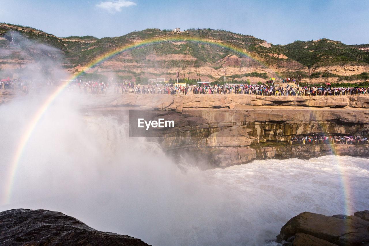 PANORAMIC VIEW OF RAINBOW OVER MOUNTAIN