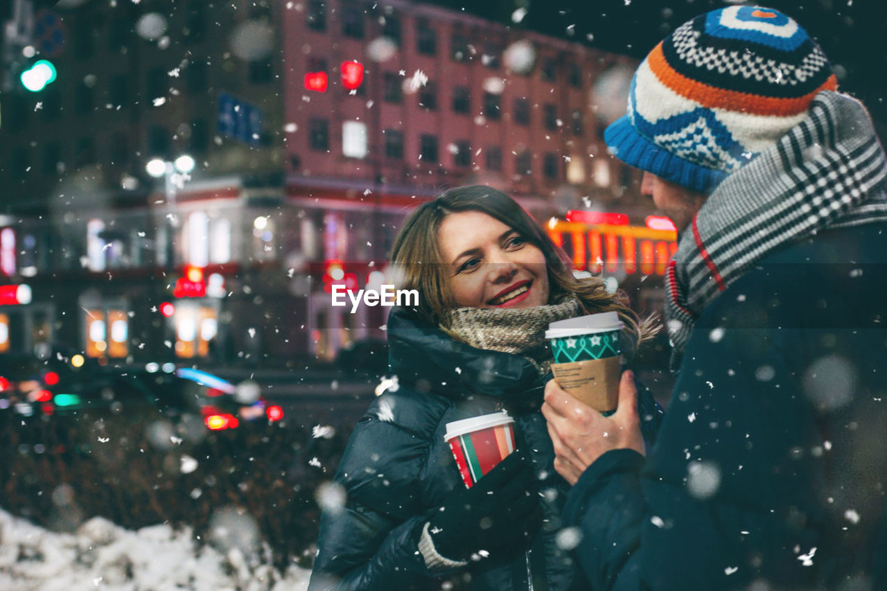 Smiling Couple Holding Disposable Cup Against Building At Night During Winter
