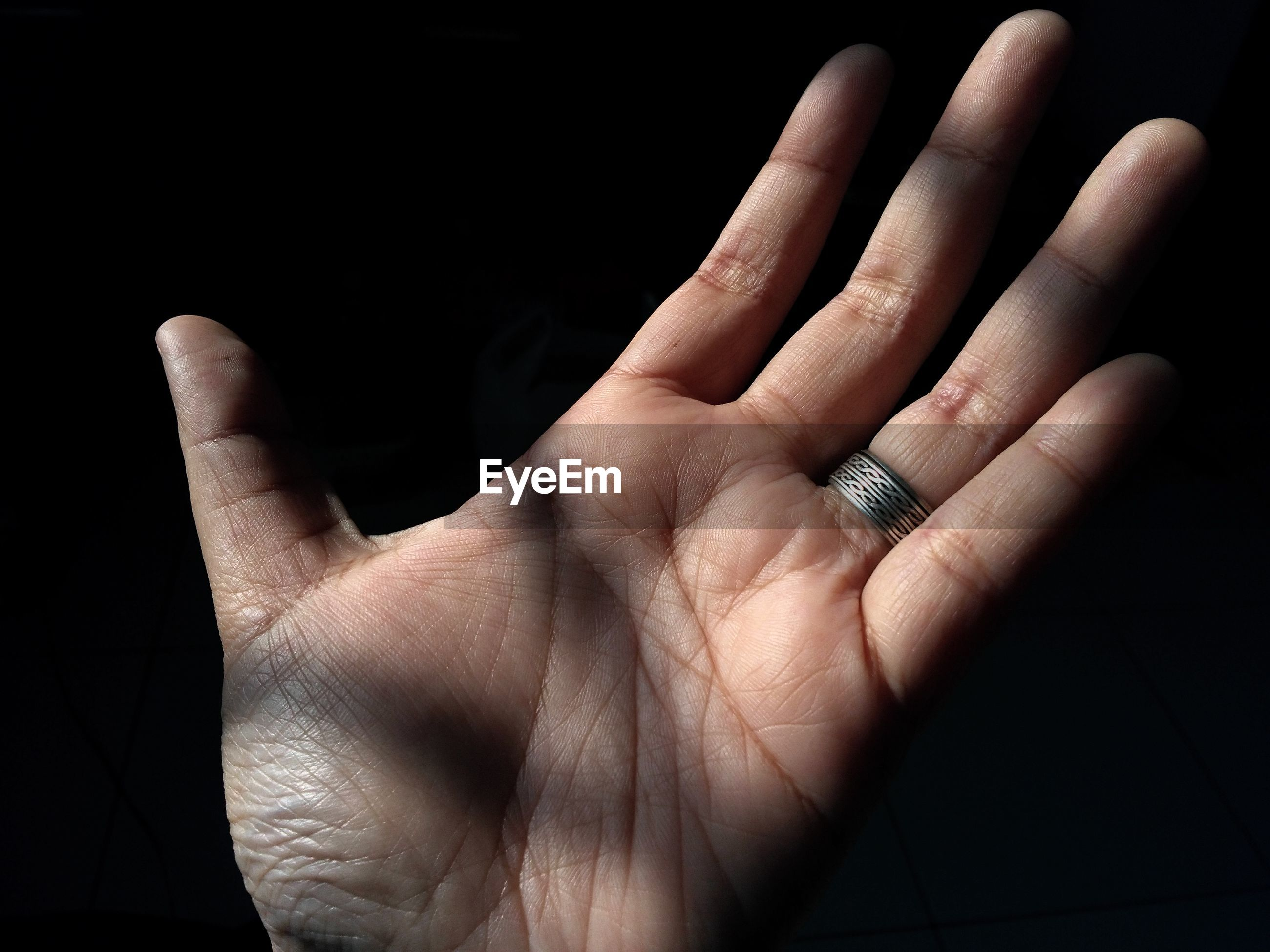 Cropped hand of woman wearing ring against black background