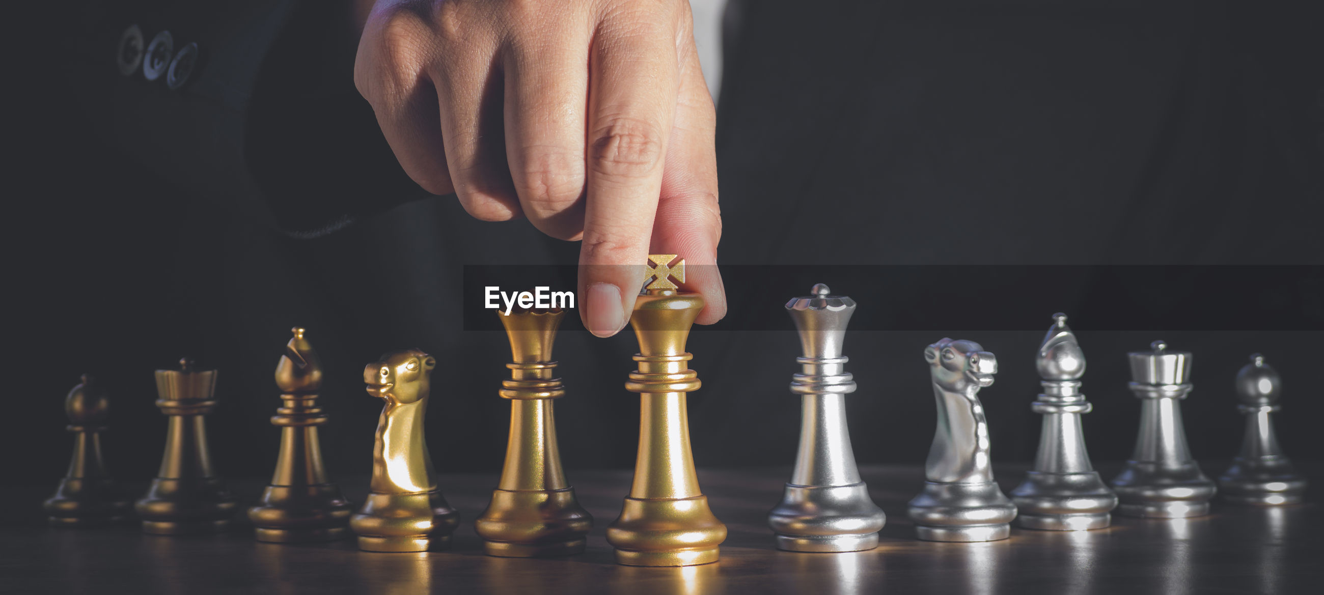 LOW ANGLE VIEW OF MAN AND CHESS PIECES ON TABLE