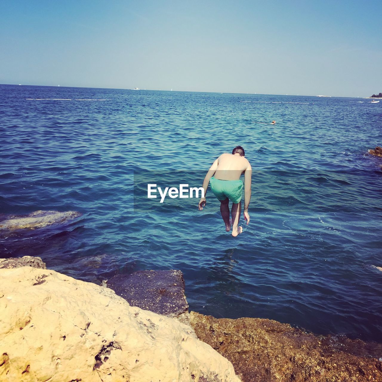 Full length of shirtless man jumping in sea against clear sky