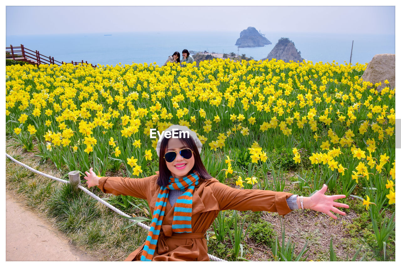 Portrait of smiling woman with arms outstretched against yellow flowering plants