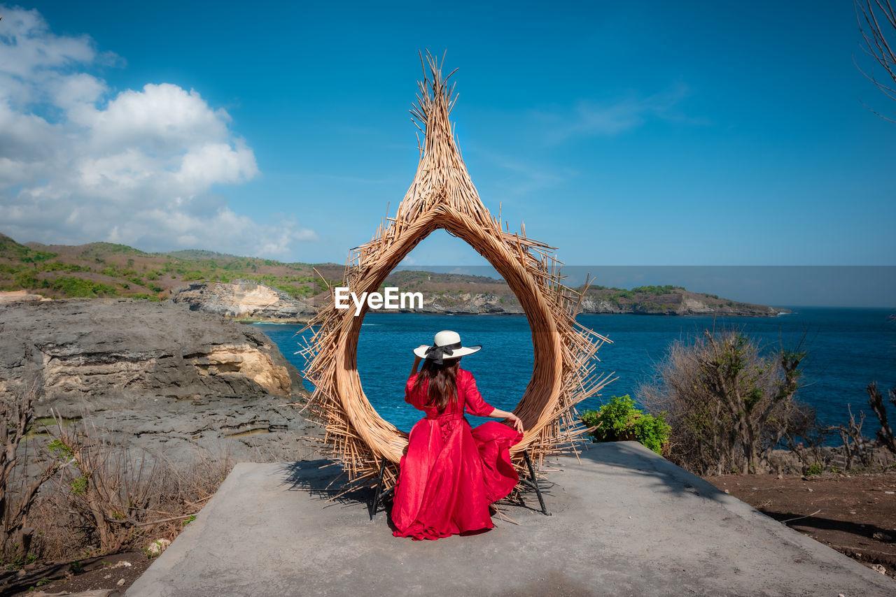 WOMAN WITH UMBRELLA AGAINST SEA