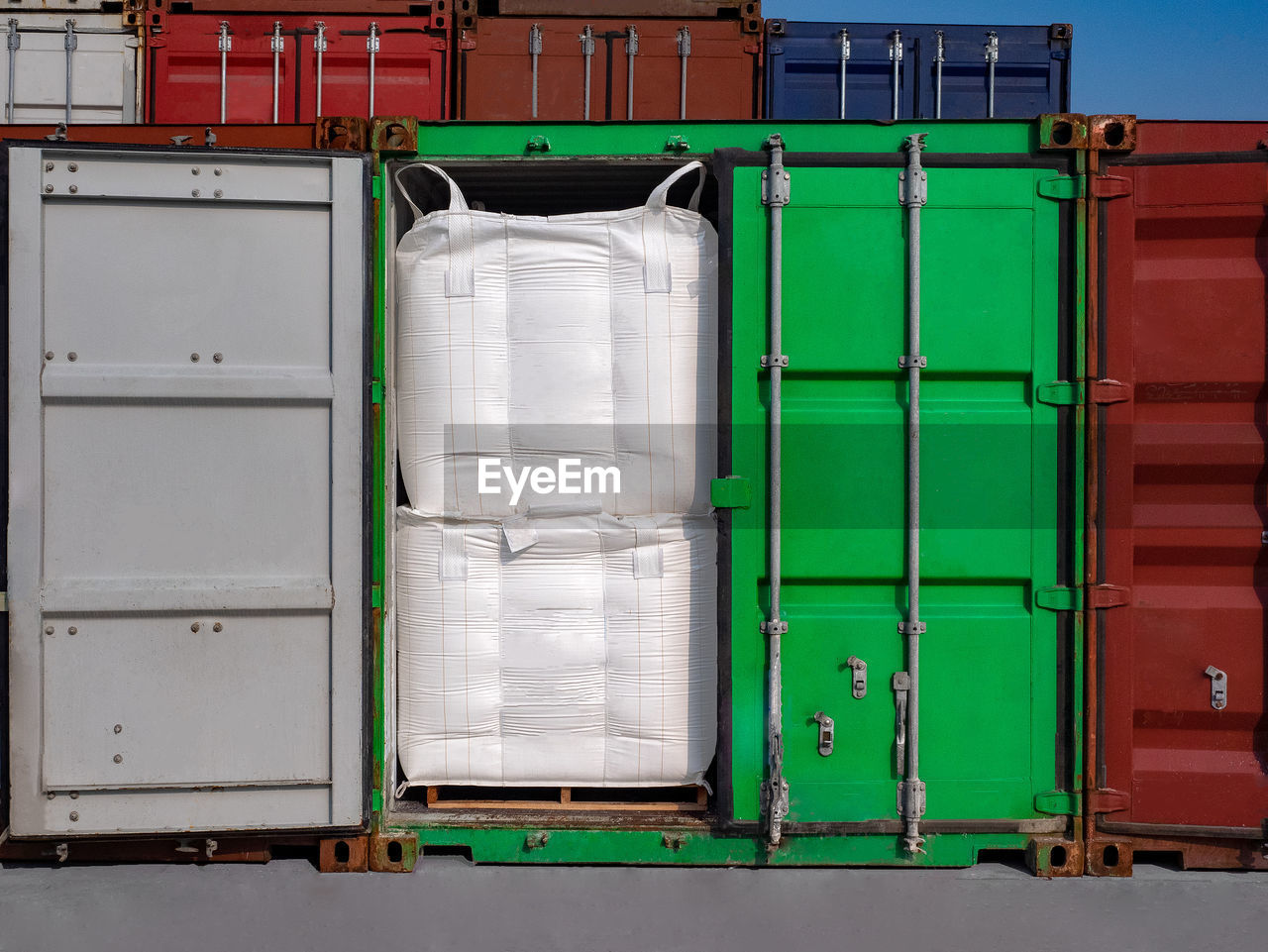 green color, container, industry, no people, architecture, box, freight transportation, white color, building, day, stack, outdoors, crate, cargo container, built structure, metal, wall - building feature, nature, business, shipping, box - container