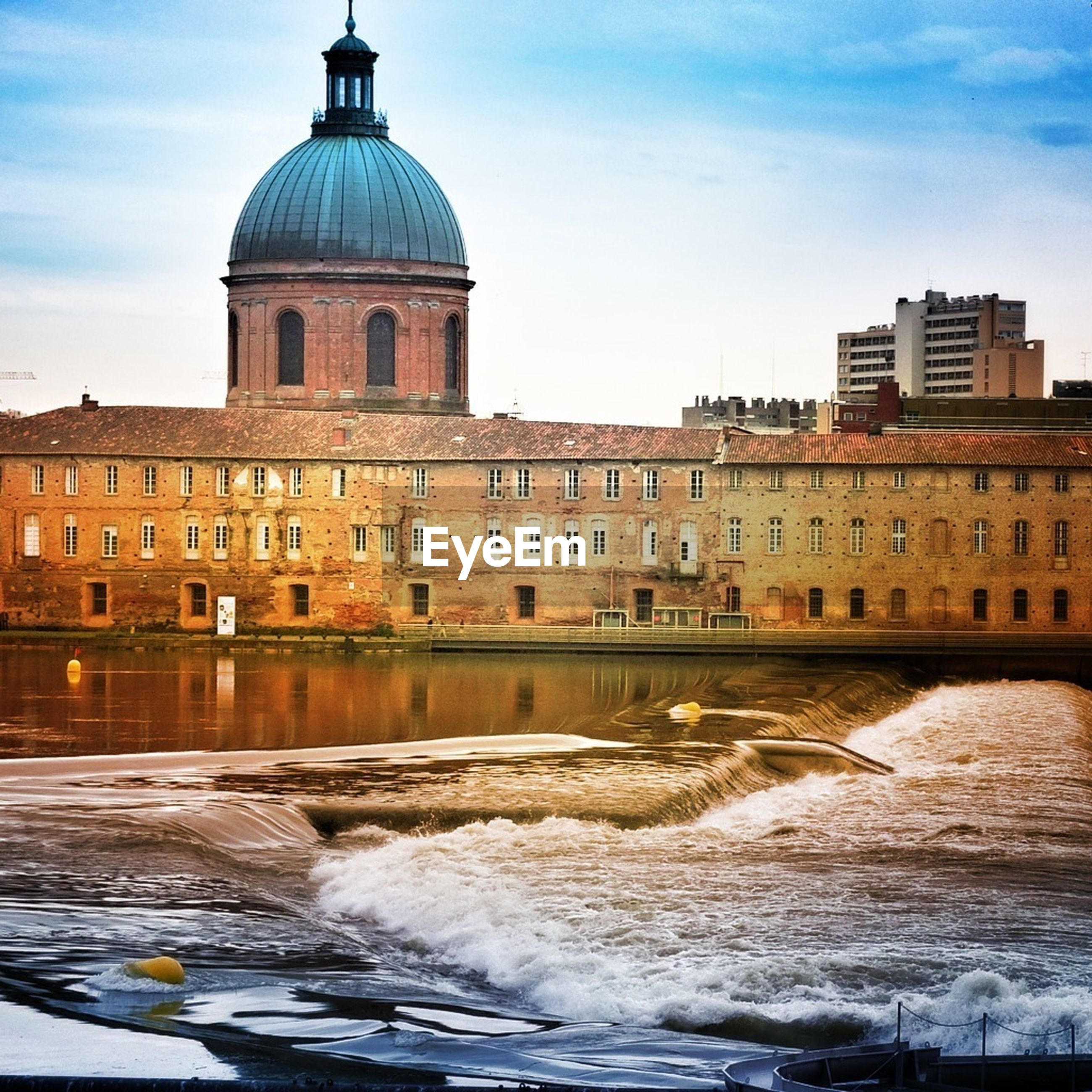 River flowing by historic building against sky
