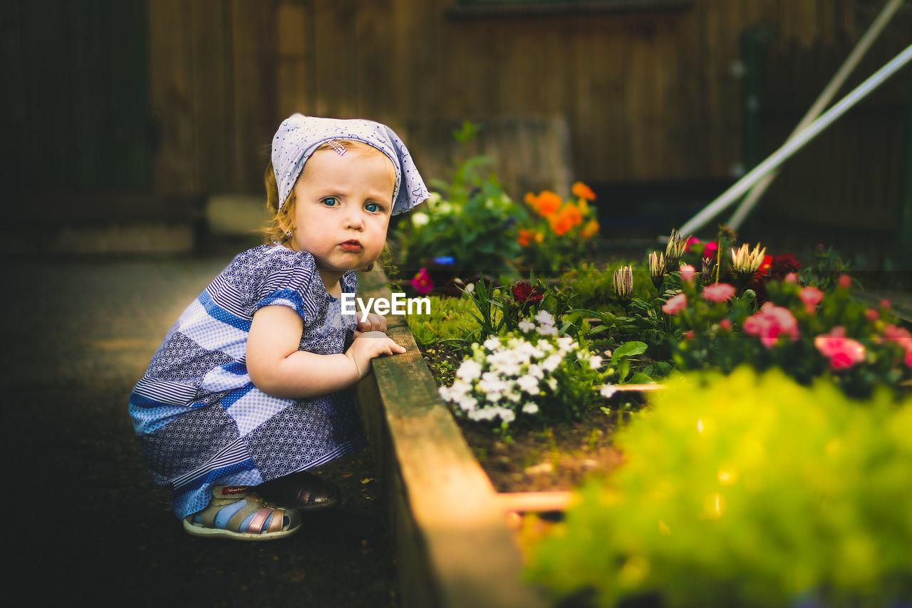 CUTE GIRL LOOKING AT FLOWER PLANTS