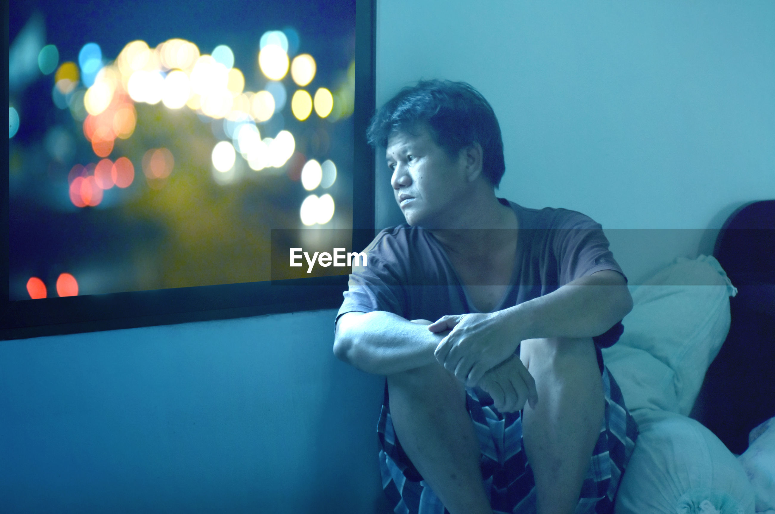 Man sitting alone on bed in mood disappointment and look at outside window with beautiful light.