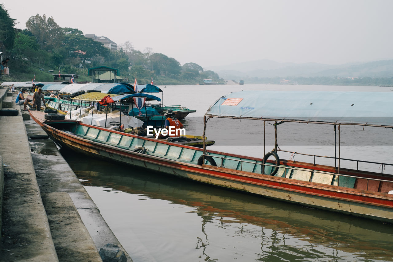 transportation, water, nautical vessel, mode of transport, river, nature, day, mountain, scenics, beauty in nature, moored, outdoors, fog, real people, sky, men, tree, people