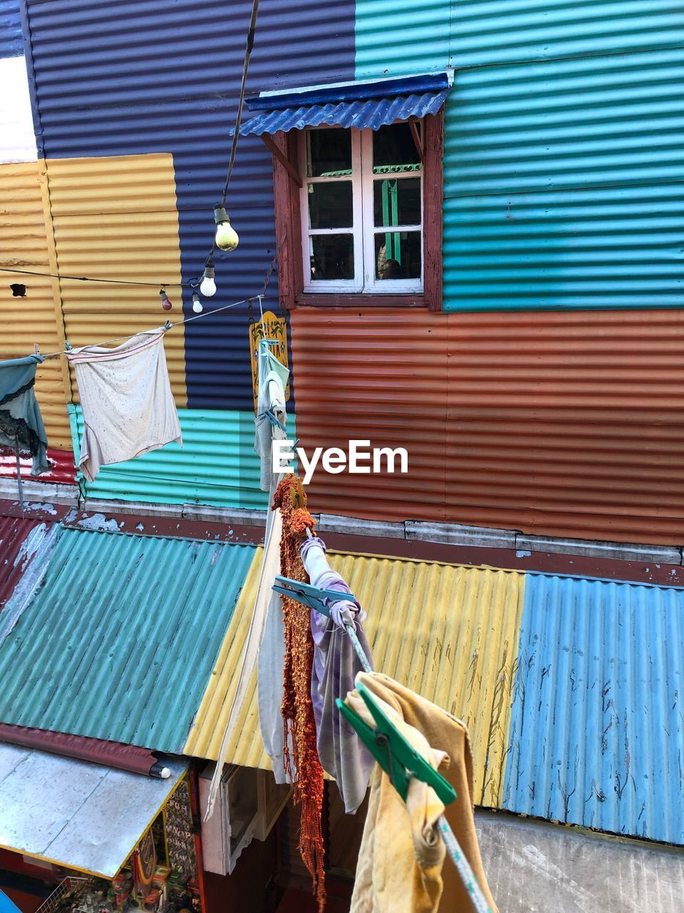 building exterior, architecture, built structure, day, shutter, corrugated iron, iron, building, drying, clothing, textile, hanging, wood - material, outdoors, house, no people, window, corrugated, cleaning, metal