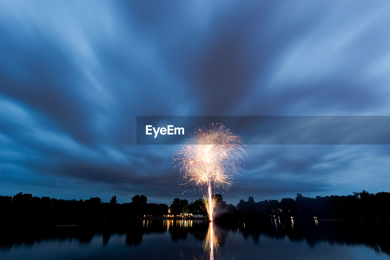 sky, firework, illuminated, water, night, arts culture and entertainment, nature, reflection, cloud - sky, celebration, long exposure, lake, motion, exploding, firework display, glowing, event, no people, smoke - physical structure, outdoors, light, firework - man made object
