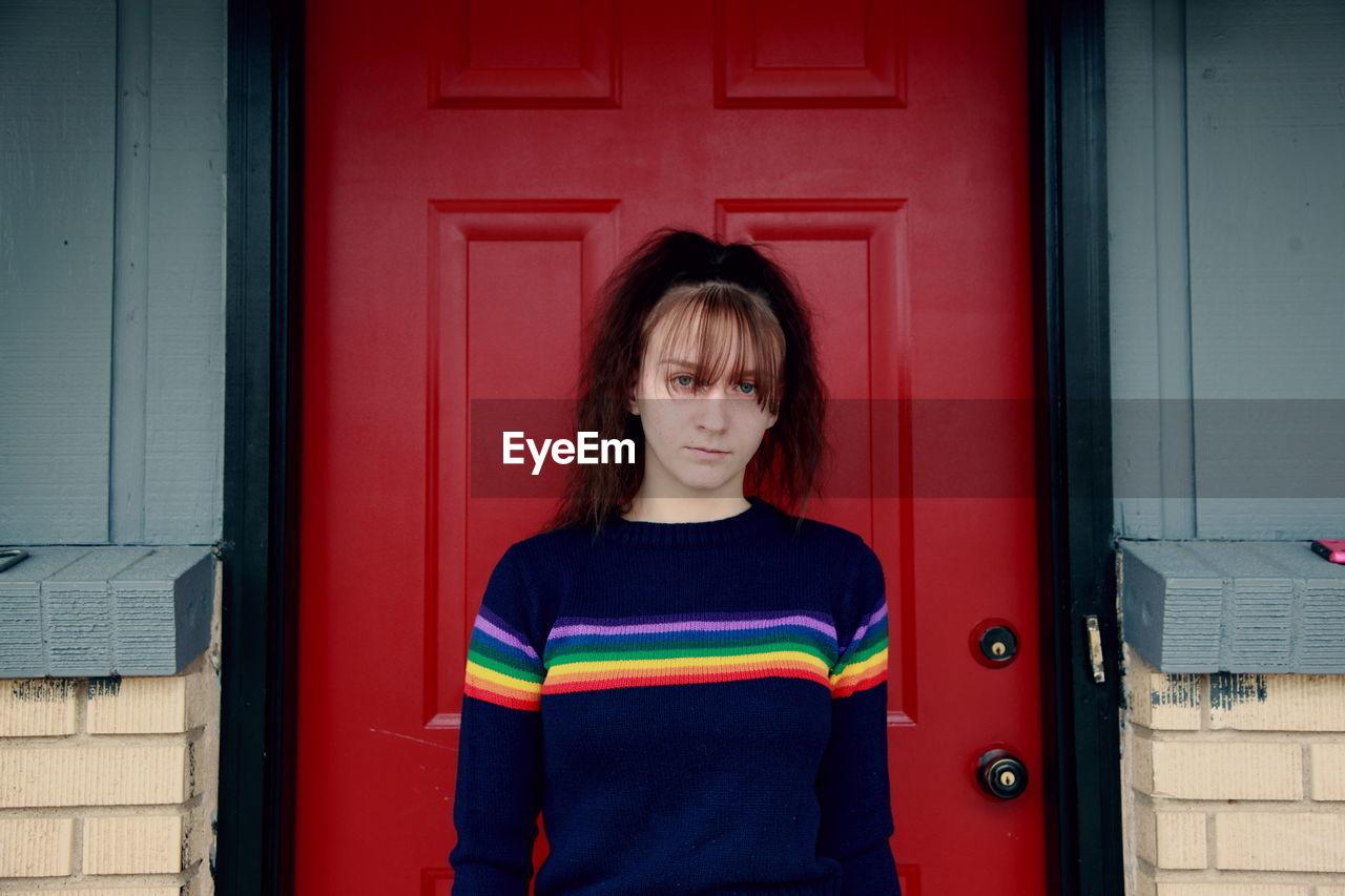 Portrait Of Teenage Girl Standing By Red Door