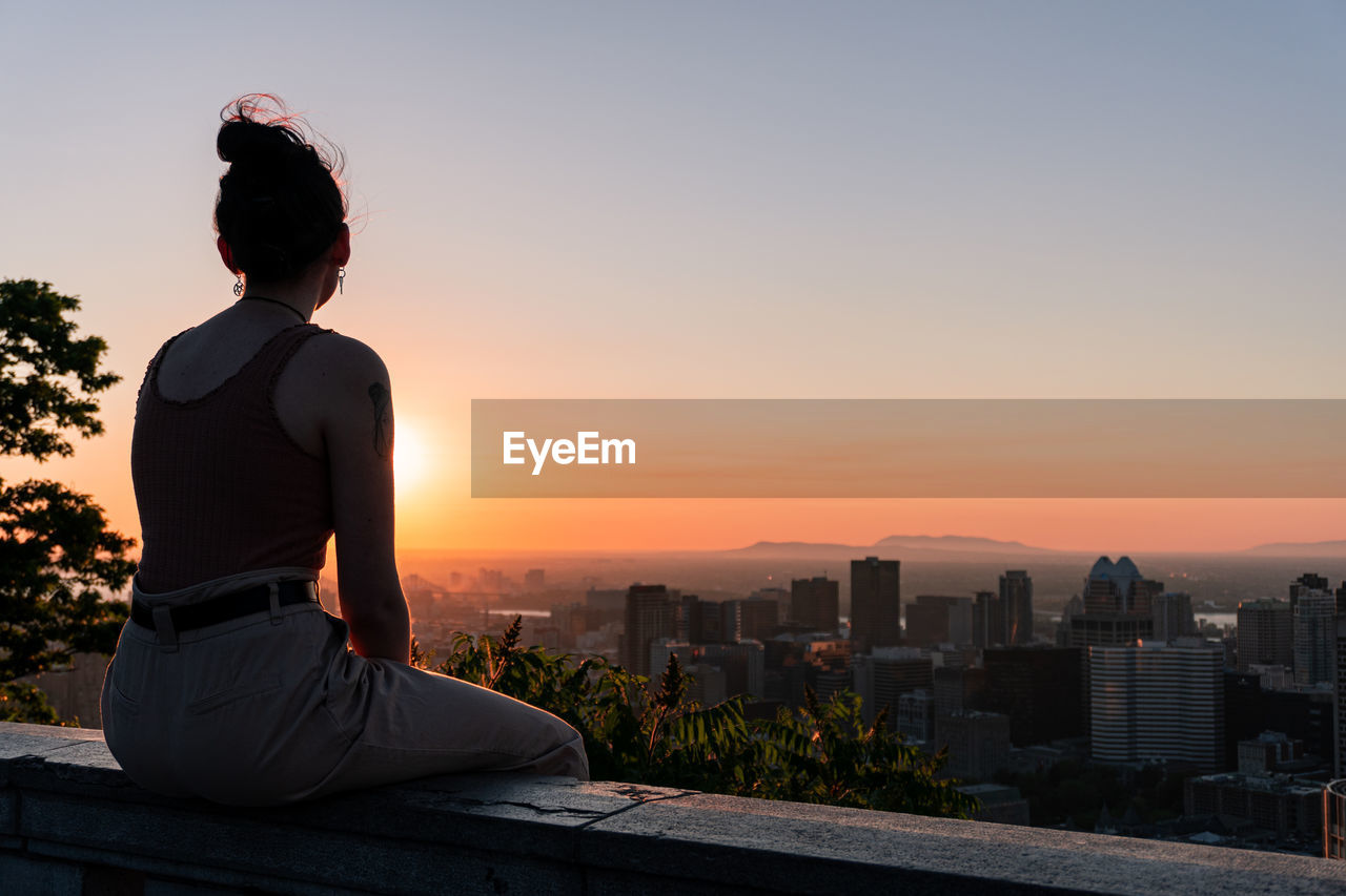 Women looking at cityscape against sky during sunset