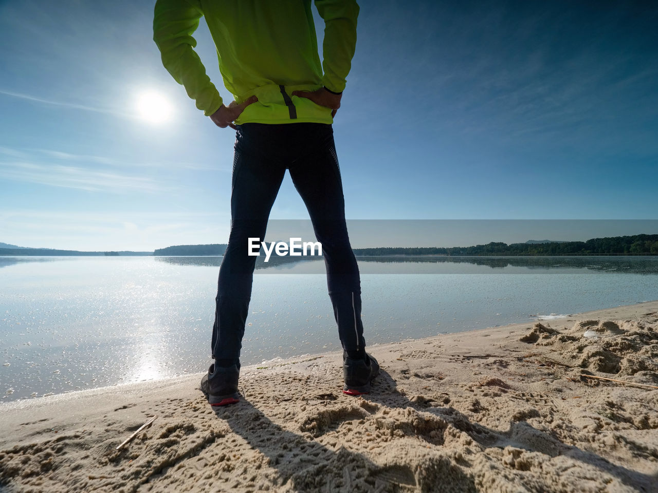 LOW SECTION OF MAN STANDING AT BEACH AGAINST SKY