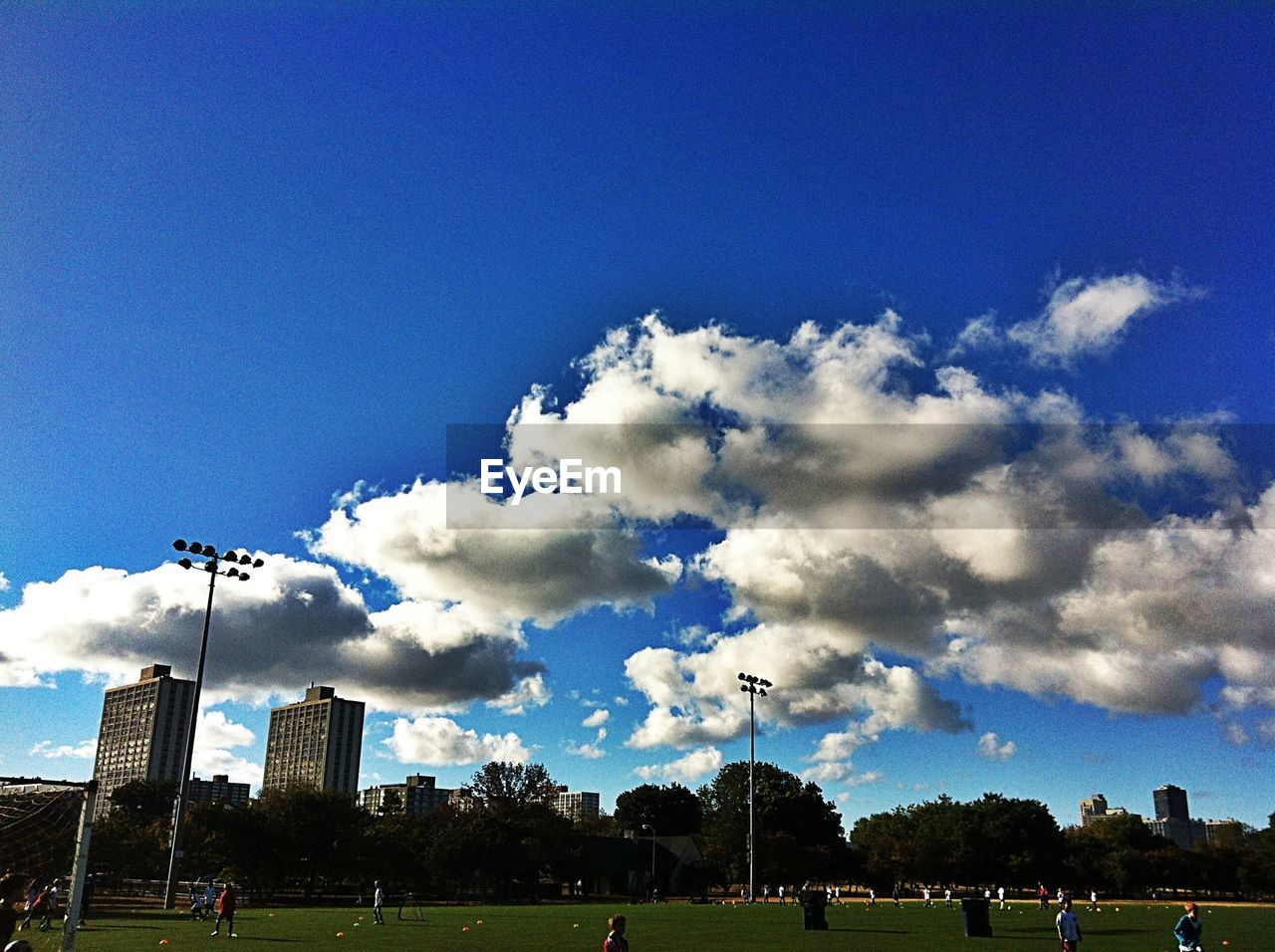 sky, large group of people, cloud - sky, arts culture and entertainment, outdoors, day, low angle view, built structure, floodlight, tree, blue, architecture, sport, nature, stadium, soccer field, people